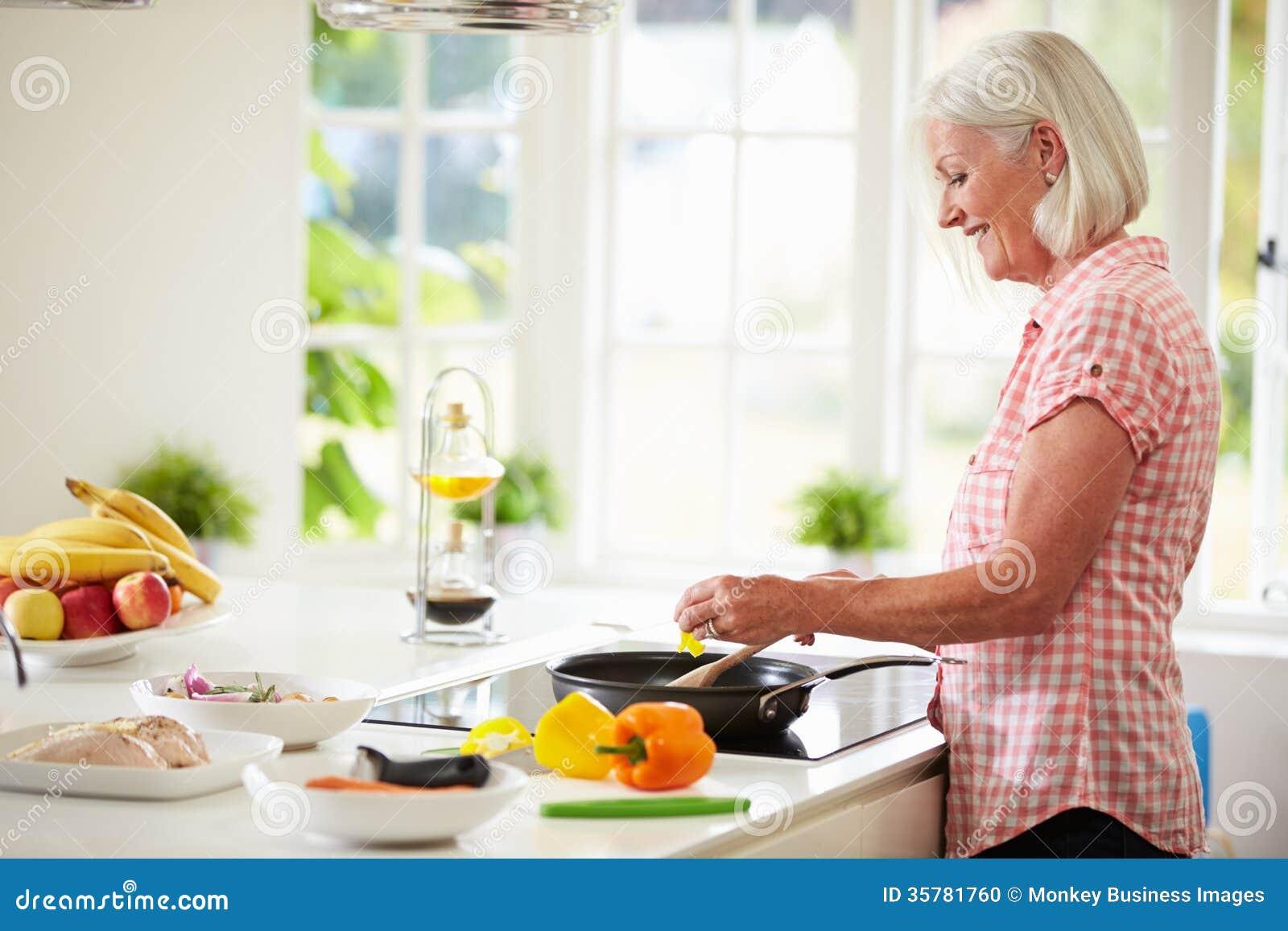 Μέσο ηλικίας μαγειρεύοντας γεύμα γυναικών στην κουζίνα