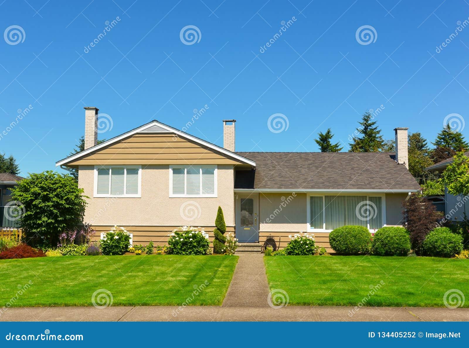 Μέσο οικογενειακό σπίτι με τον πράσινο χορτοτάπητα και δέντρα στο μέτωπο στο υπόβαθρο μπλε ουρανού