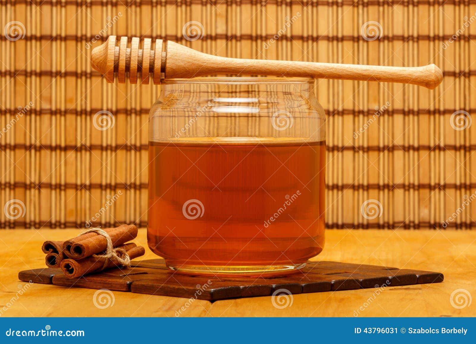 Μέλι στο βάζο με dipper και κανέλας τους φραγμούς