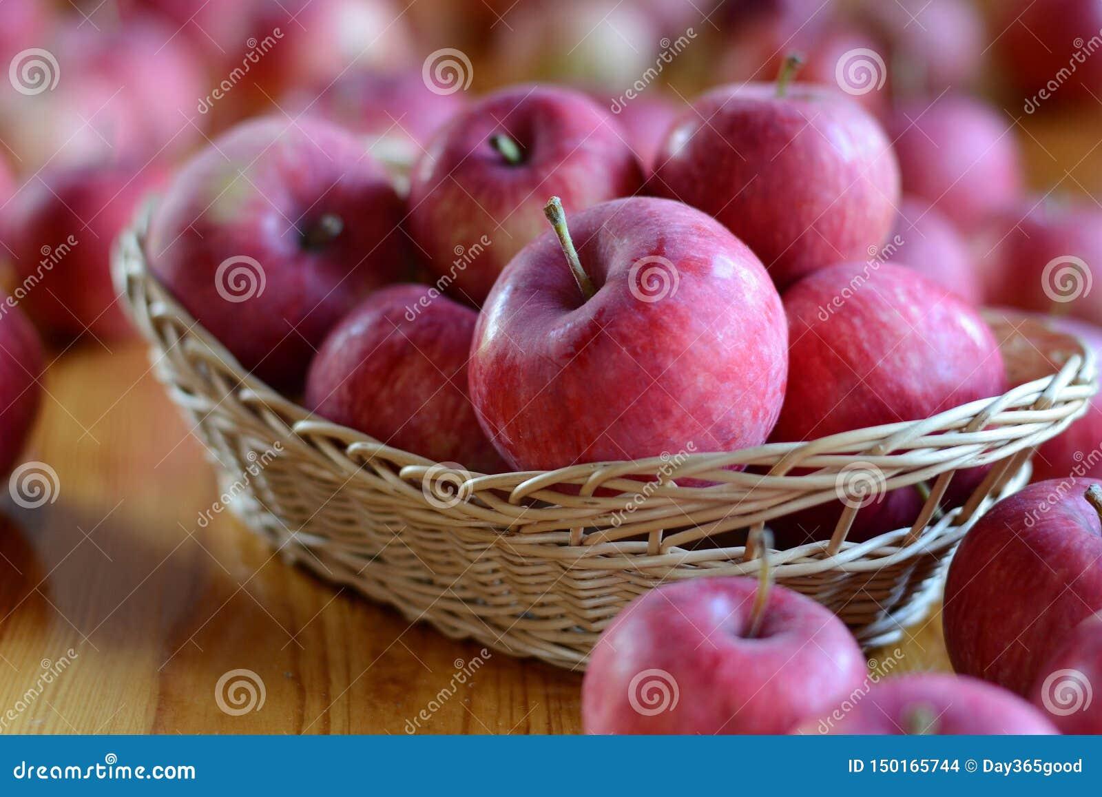 Μήλα στο καλάθι στο ξύλινο υπόβαθρο Χρόνος συγκομιδών, φθινόπωρο, πολλά κόκκινα μήλα