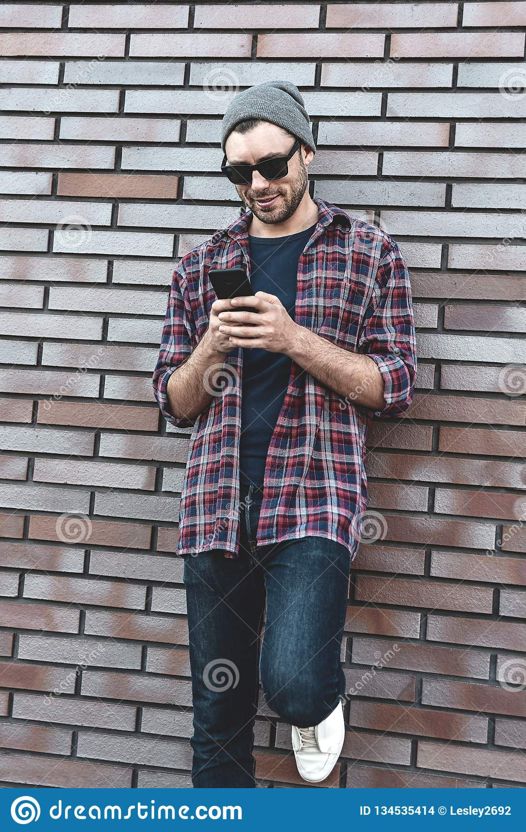 Μήνυμα κειμένου δακτυλογράφησης Πλάγια όψη του όμορφου νεαρού άνδρα στην έξυπνη περιστασιακή ένδυση που κρατά το κινητό τηλέφωνο