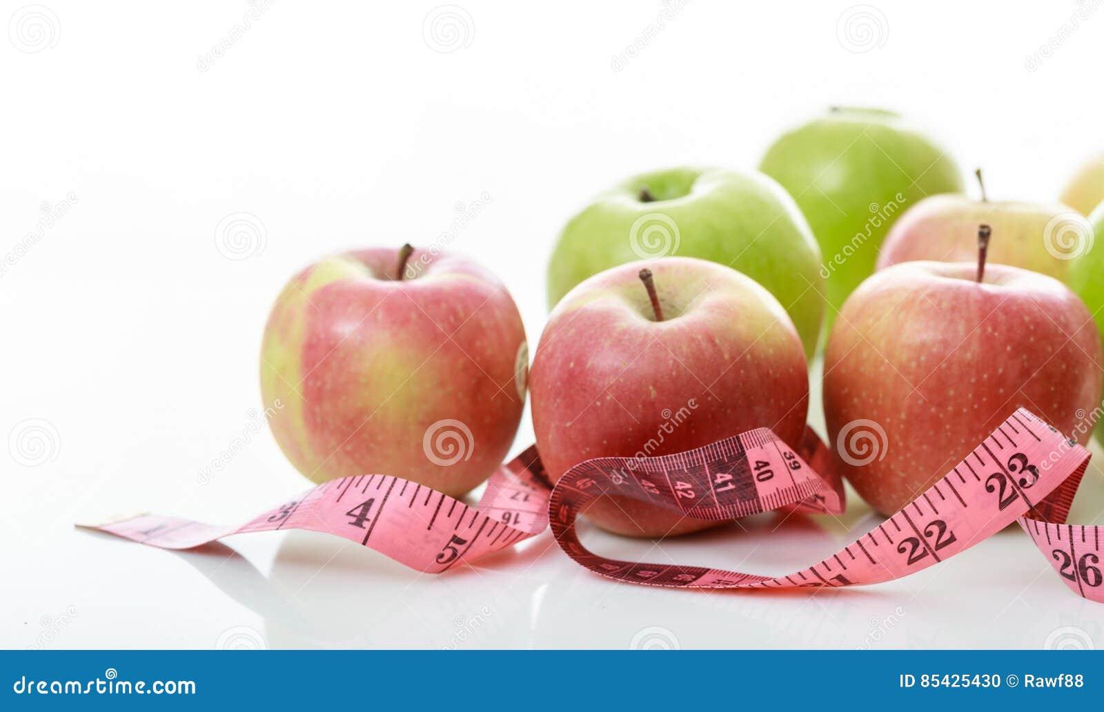 Μήλα και ταινία μέτρου στο άσπρο υπόβαθρο