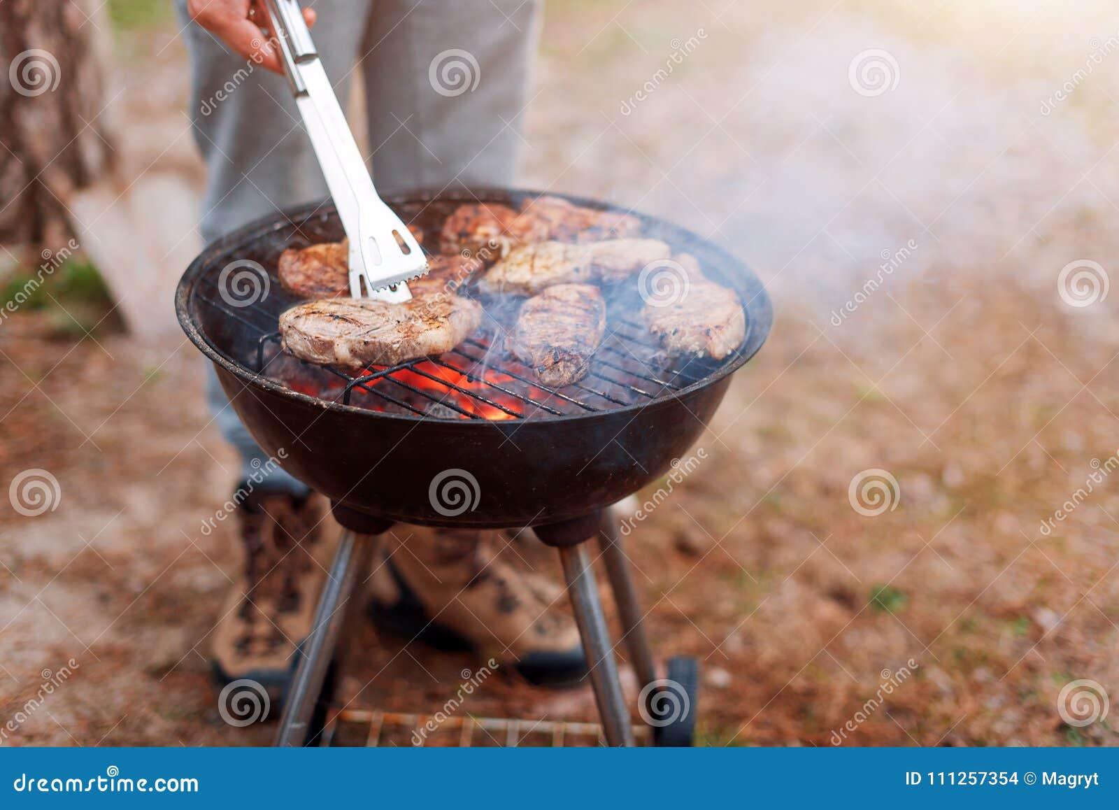 Μαγείρεμα ατόμων, μόνο χέρια, ψήνει το κρέας ή την μπριζόλα για ένα πιάτο στη σχάρα Εύγευστο ψημένο στη σχάρα κρέας στη σχάρα Σαβ