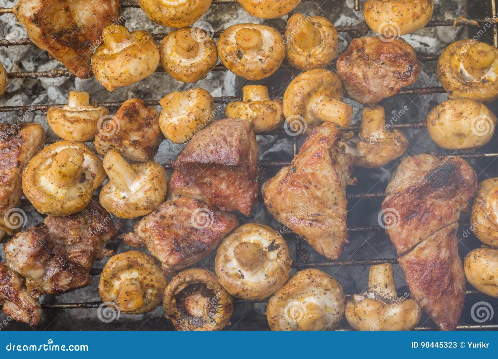 Μαγείρεμα κρέατος με τα μανιτάρια τομέων υπαίθρια στους σιγοκαίγοντας άνθρακες