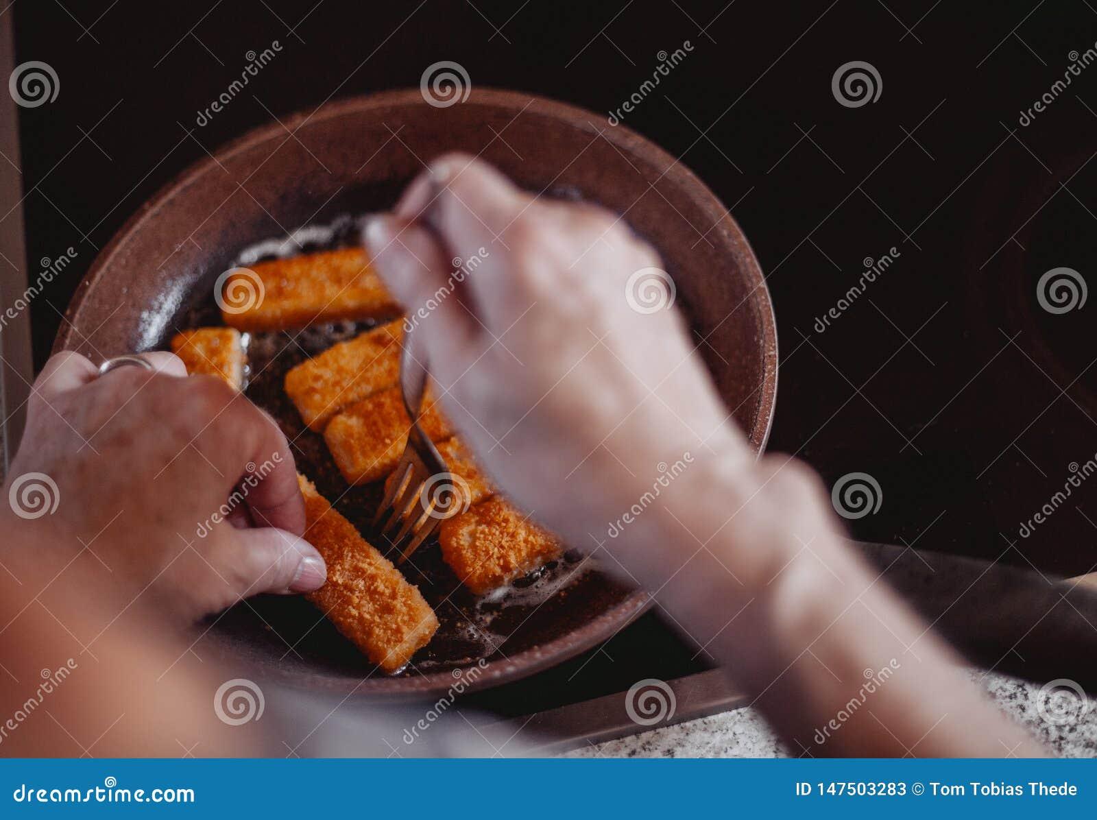 Μαγείρεμα των εύγευστων δάχτυλων ψαριών στο τηγάνι