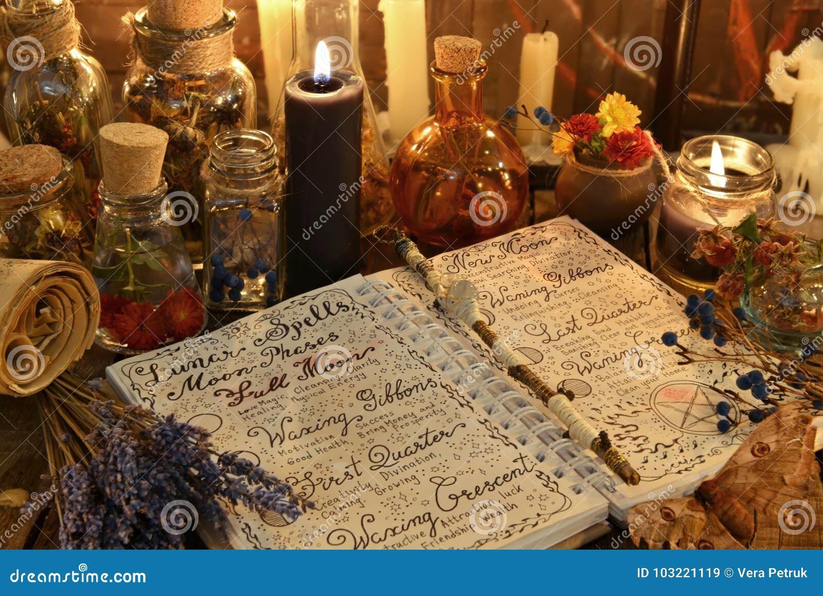 Μαγικό βιβλίο με τις περιόδους, lavender τη δέσμη και το μαύρο κερί στον πίνακα μαγισσών