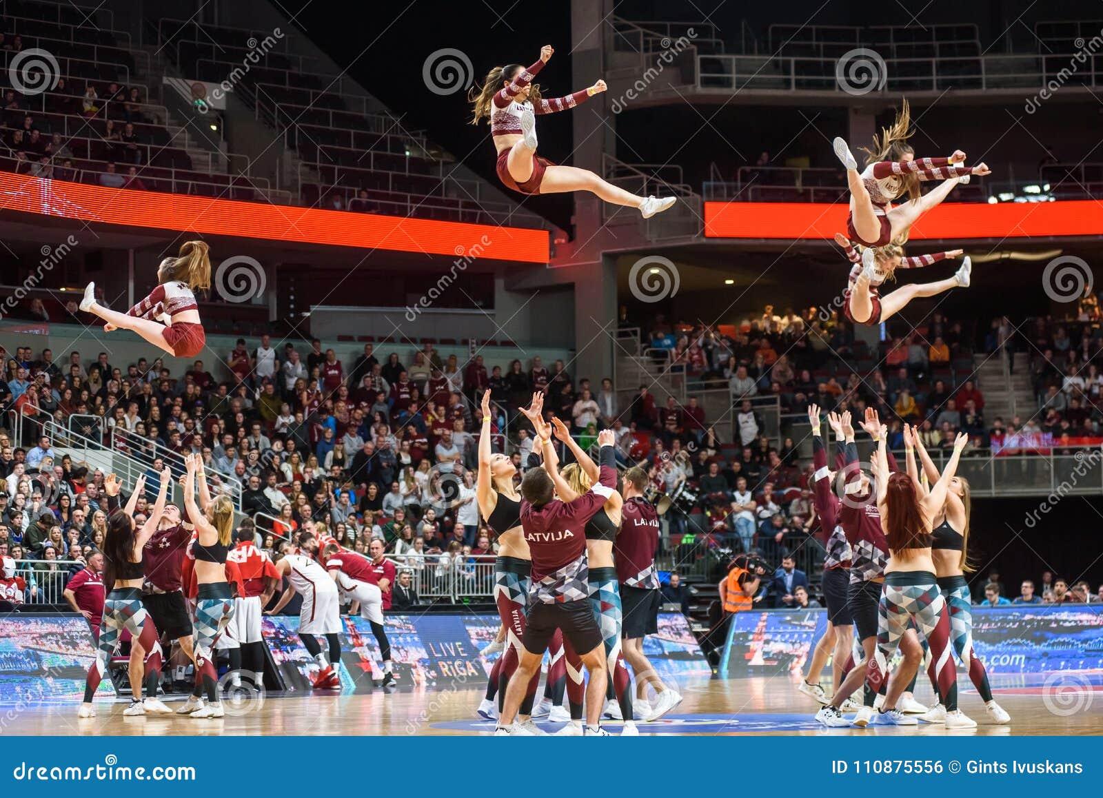 Μαζορέτες που πηδούν στον αέρα, κατά τη διάρκεια της απόδοσης στο μισό χρόνο πετώντας στεφάνη παιχνιδιών καλαθοσφαίρισης σφαιρών