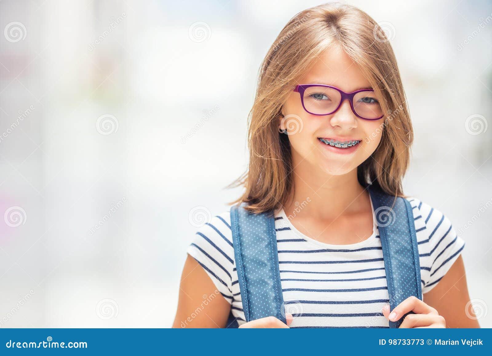 Μαθήτρια με την τσάντα, σακίδιο πλάτης Πορτρέτο του σύγχρονου ευτυχούς σχολικού κοριτσιού εφήβων με το σακίδιο πλάτης τσαντών Κορ