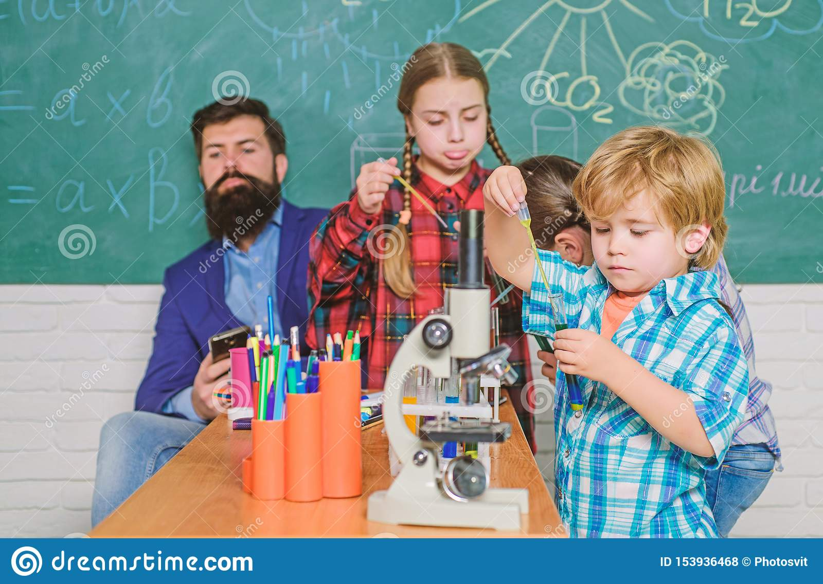 Μαθητής που εξετάζει μέσω του μικροσκοπίου το δημοτικό σχολείο πειραματισμός με τις χημικές ουσίες ή μικροσκόπιο στο εργαστήριο