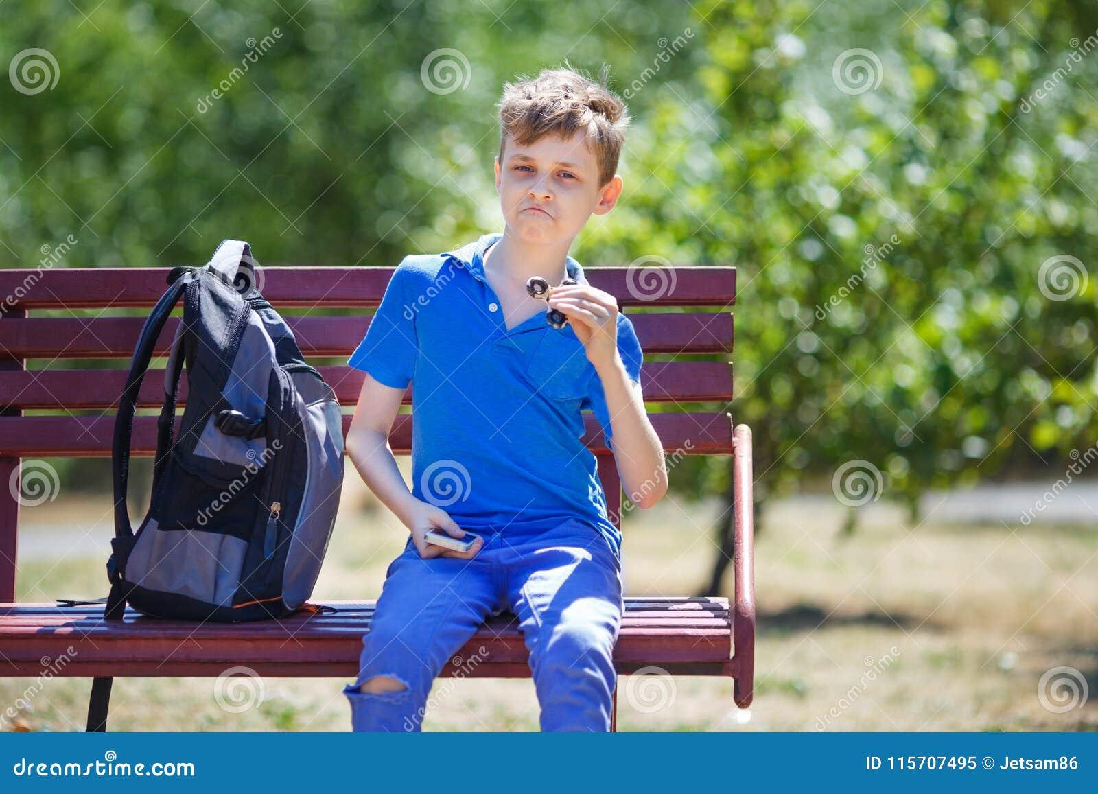 Μαθητής που μορφάζει, παιδί που καυχάται με fidget τον κλώστη διασκεδάστε