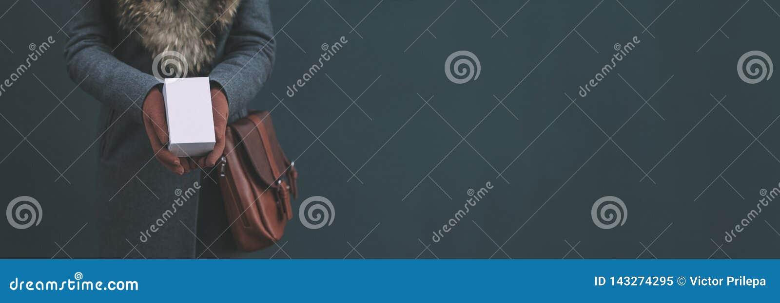 Μακρύ έμβλημα με τη χλεύη επάνω ένα άσπρο κιβώτιο από ένα smartphone Το κορίτσι σε ένα παλτό και καφετιά γάντια κρατά ένα δώρο στ