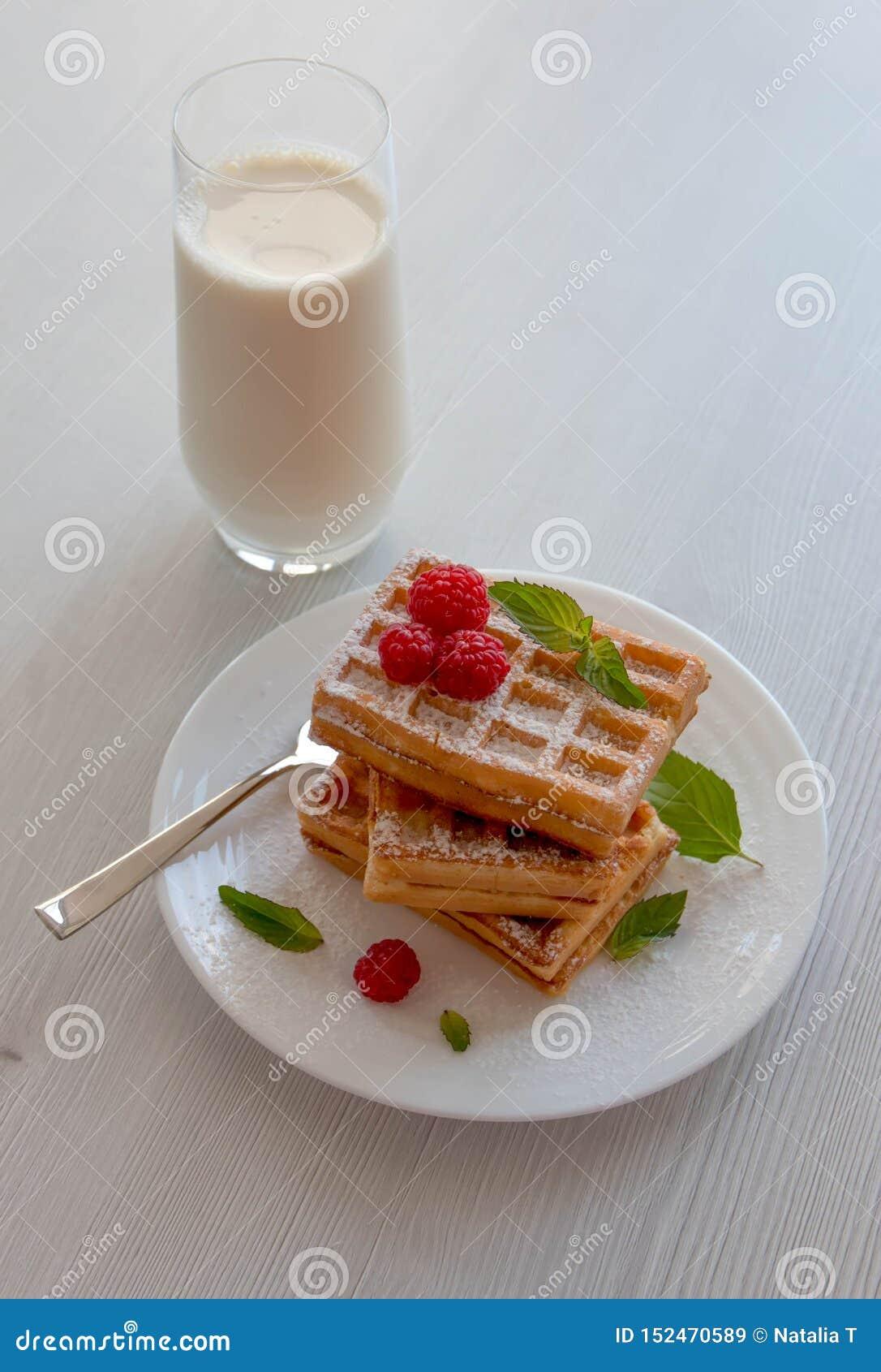 Μαλακές βάφλες με τα σμέουρα και ένα ποτήρι του γάλακτος, σε ένα άσπρο υπόβαθρο