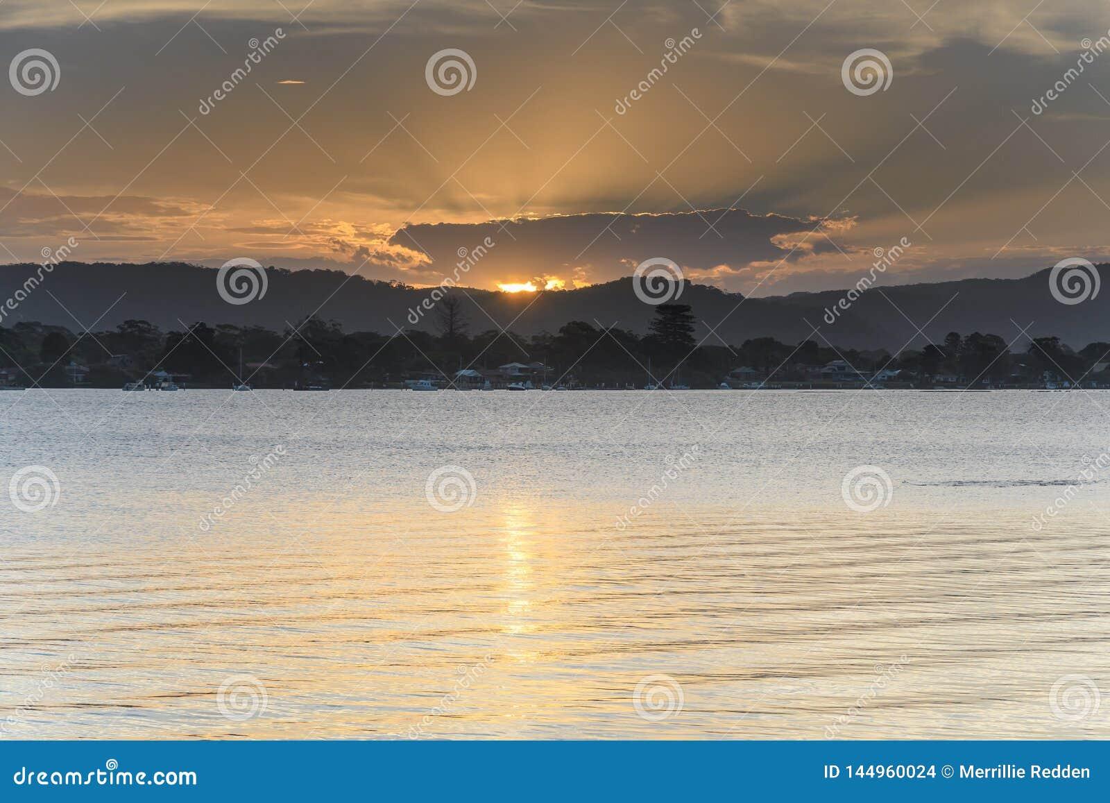 Μαλακό χρυσό ηλιοβασίλεμα πέρα από τον κόλπο με το υψηλό σύννεφο