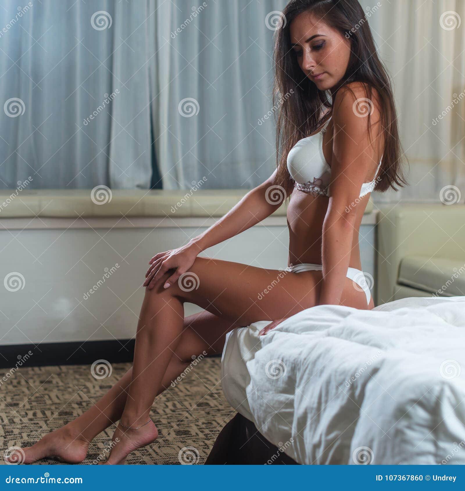 Μαυρισμένη λεπτή νέα γυναίκα brunette που φορά τον άσπρο στηθόδεσμο που θέτει τη συνεδρίαση στο κρεβάτι στην ελαφριά κρεβατοκάμαρ
