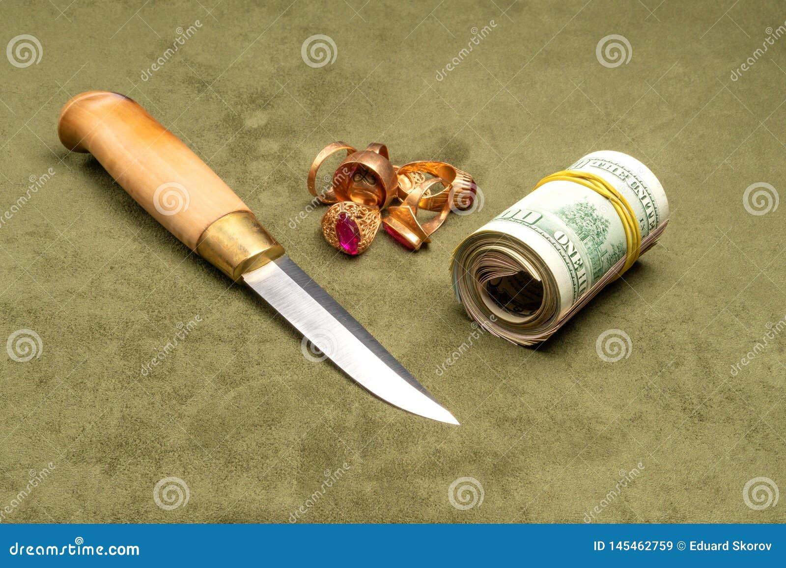 Μαχαίρι και δολάρια και χρυσός σε ένα πράσινο υπόβαθρο
