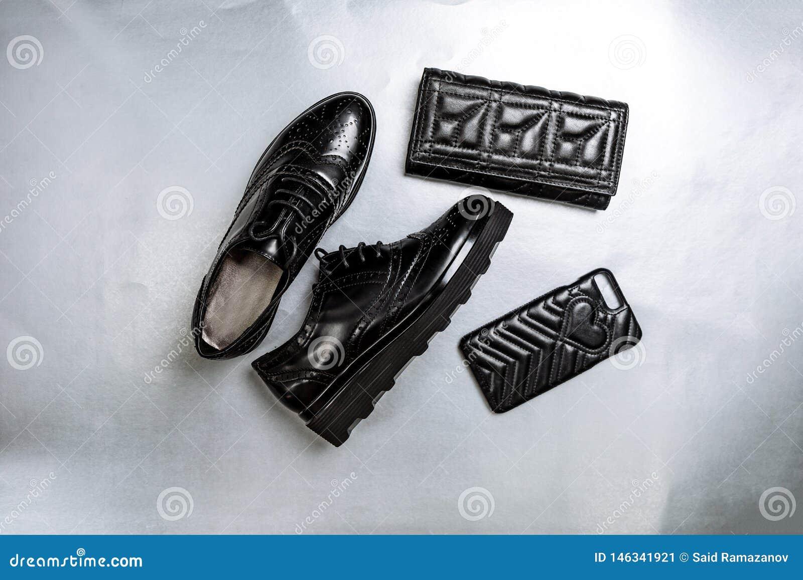 Μαύρα διατρυπημένα oxfords παπουτσιών, ένα πορτοφόλι και μια τηλεφωνική περίπτωση σε ένα άσπρο υπόβαθρο εγγράφου