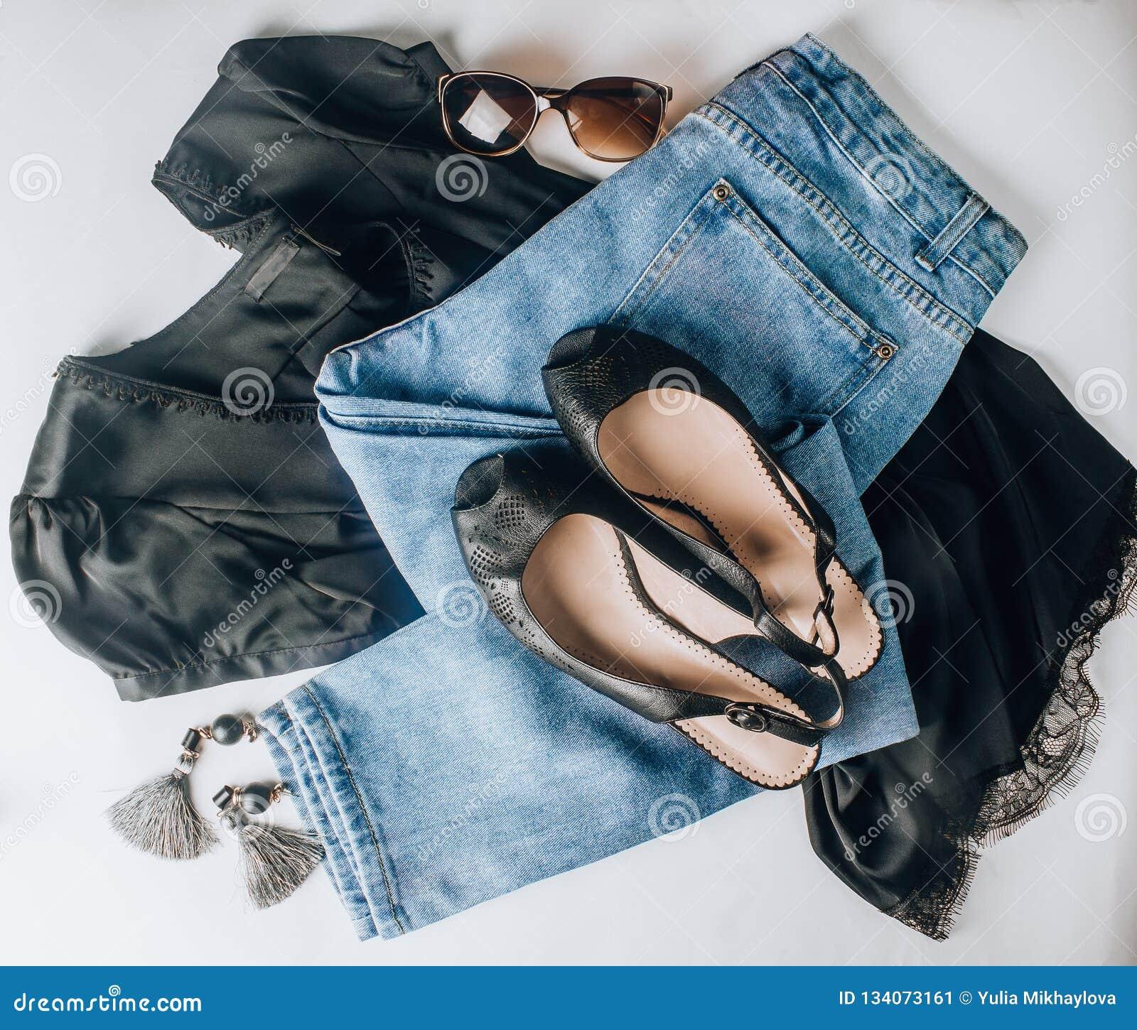 Μαύρα παπούτσια δέρματος, τζιν παντελόνι, μαύρες μπλούζες μεταξιού, γυαλιά ηλίου και σκουλαρίκια μπλε έξυπνη γυναίκα μόδας προσώπ