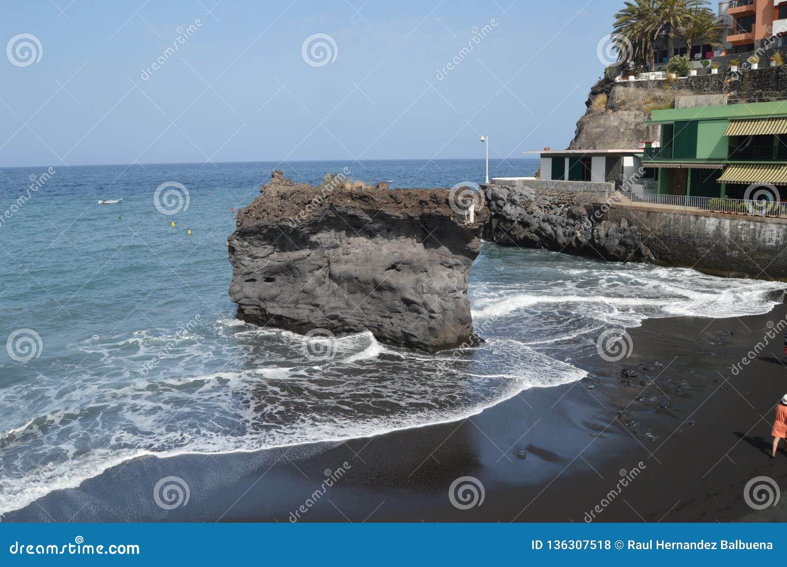 Μαύρη παραλία άμμου με το μεγάλο Stone στο εσωτερικό του στους NAO (Εθνικός Οργανισμός Διαιτησίας) Puerto στην πόλη του Los Llano