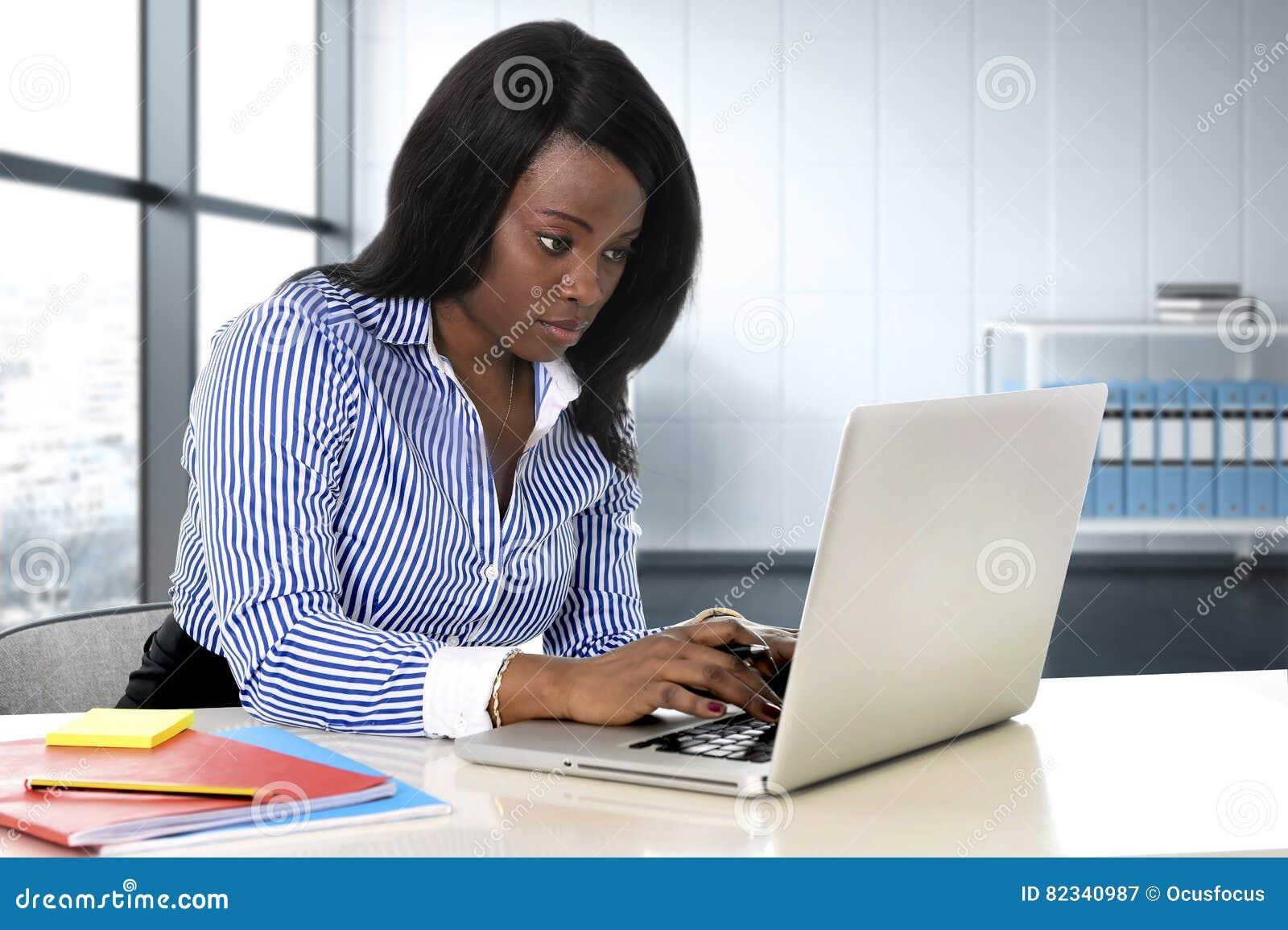 Μαύρη συνεδρίαση γυναικών έθνους στο γραφείο lap-top υπολογιστών που δακτυλογραφεί τη συγκεντρωμένη εργασία