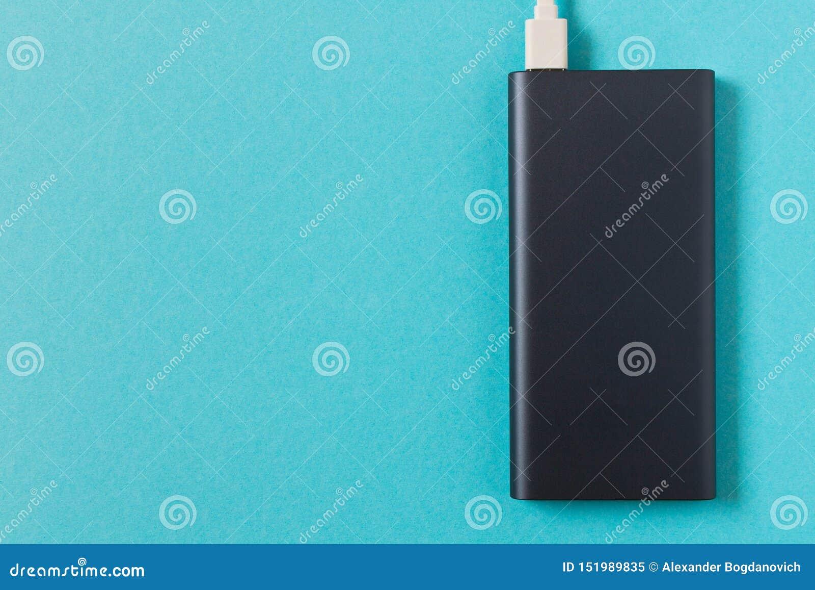 Μαύρη τράπεζα δύναμης με τον προσαρμοστή για τη χρέωση των κινητών συσκευών σε ένα μπλε υπόβαθρο