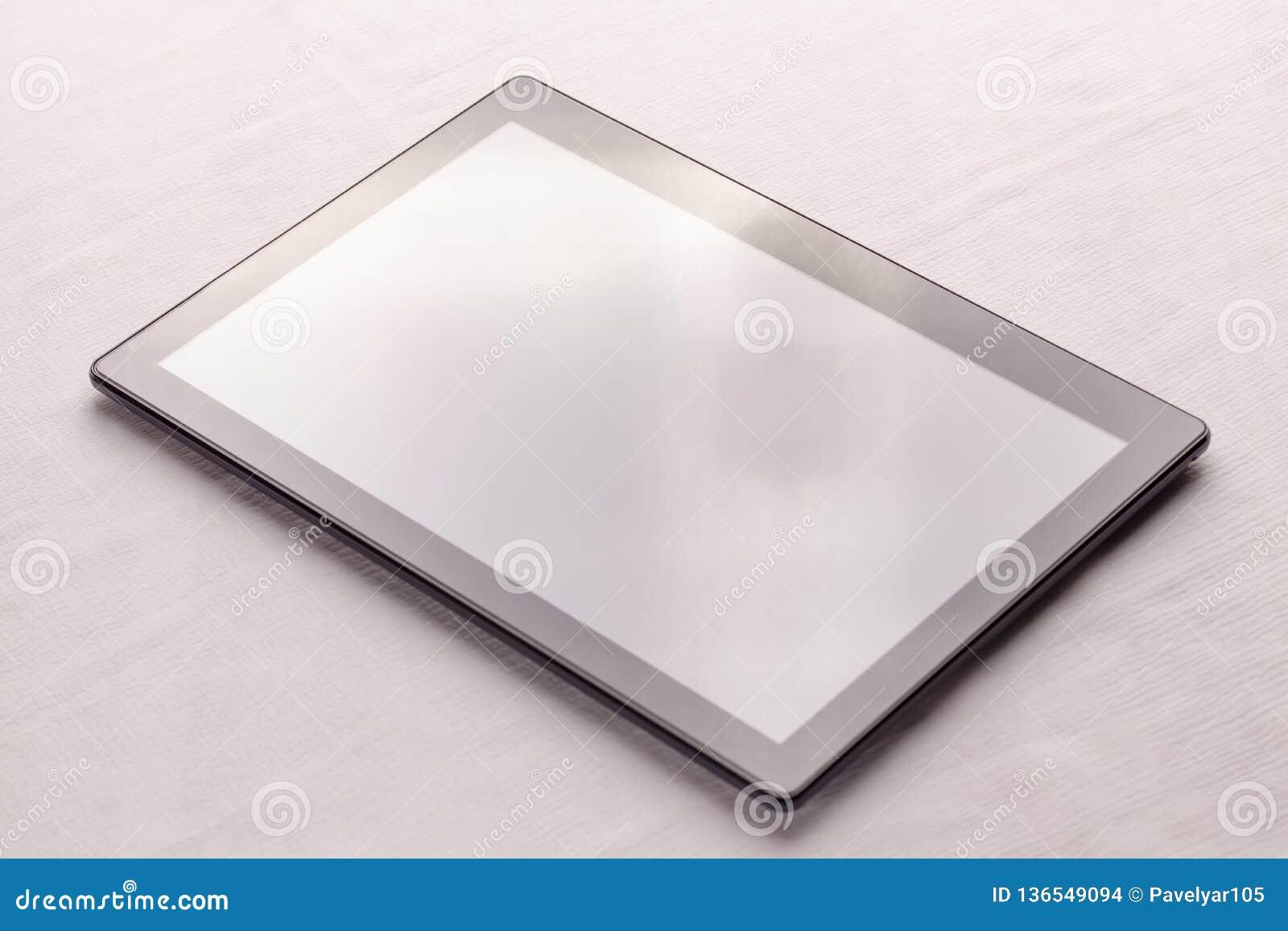 Μαύρη ψηφιακή ταμπλέτα στο άσπρο ύφασμα