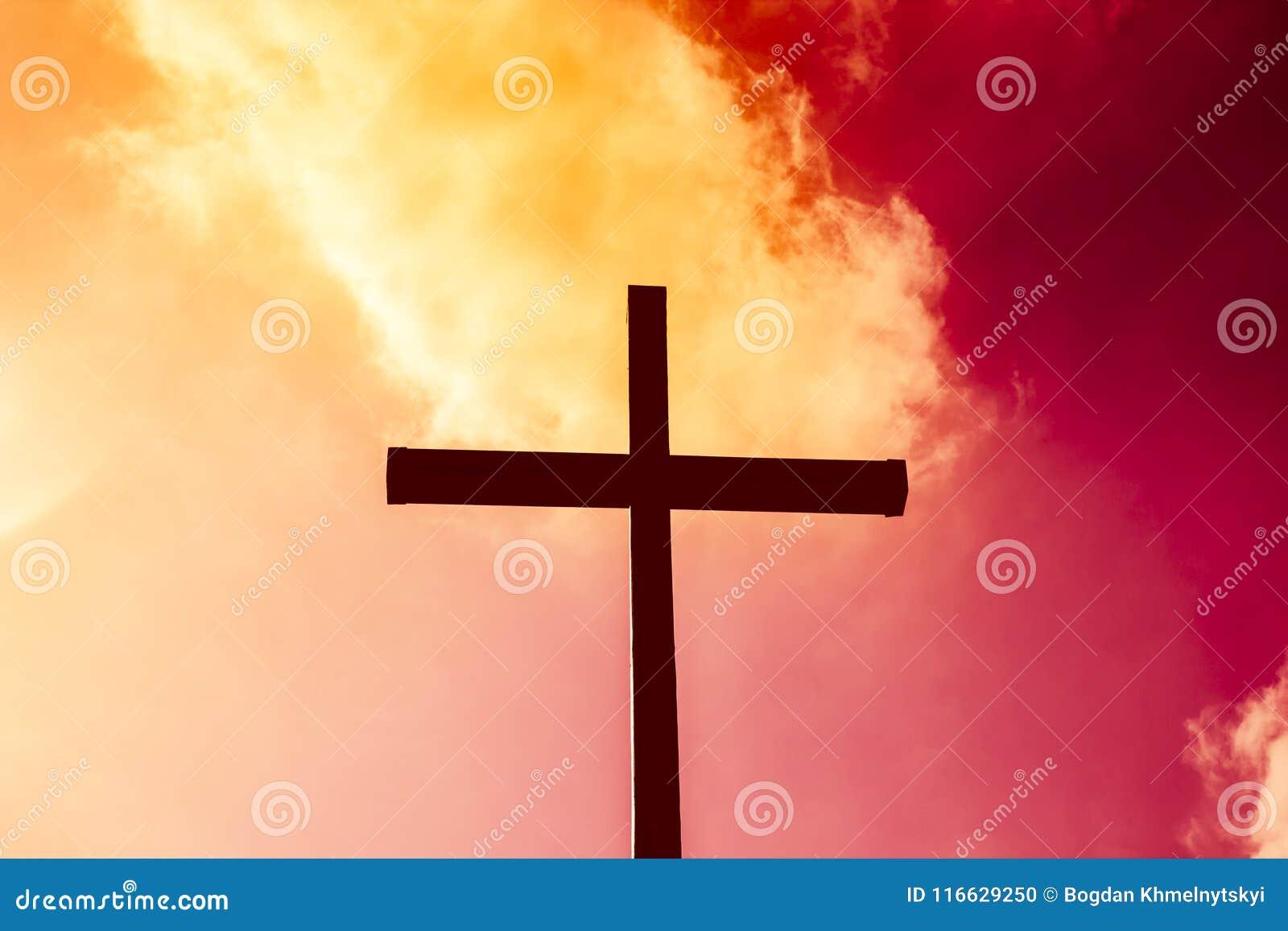 Μαύρος σταυρός σε ένα υπόβαθρο του κόκκινου και κίτρινου φλεμένος ουρανού, από