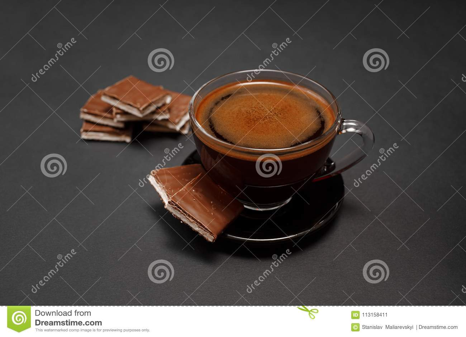 Μαύρος, φυσικός, ευώδης καφές στο διαφανές φλυτζάνι σε ένα μαύρο υπόβαθρο, με τη σοκολάτα γάλακτος