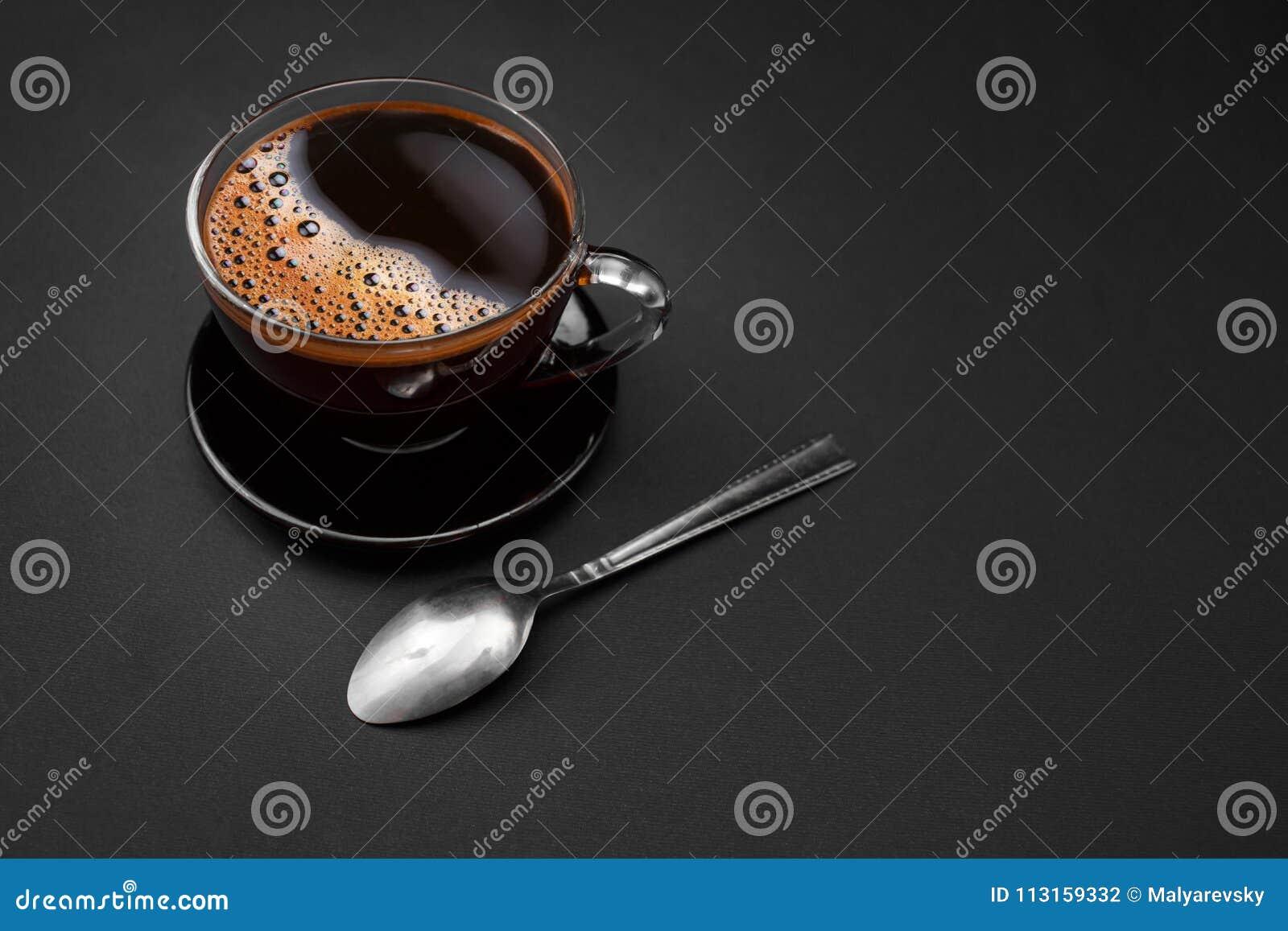 Μαύρος, φυσικός, ευώδης καφές στο διαφανές φλυτζάνι σε ένα μαύρο υπόβαθρο