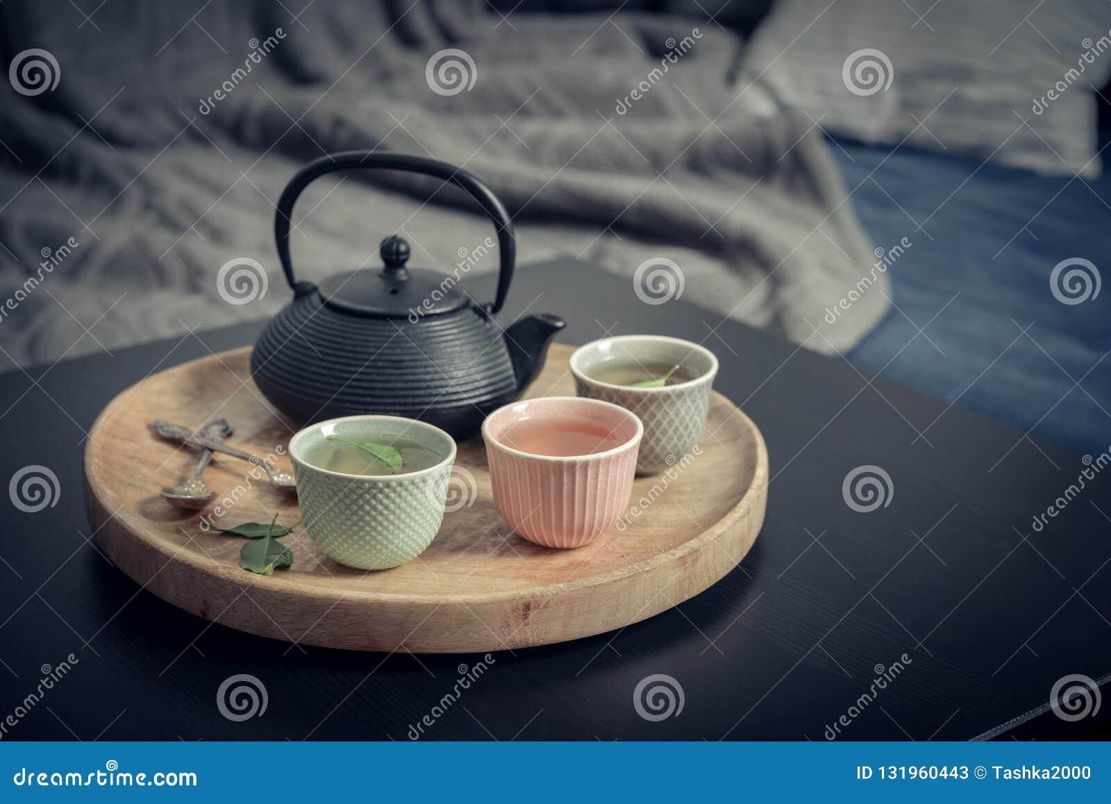 Μαύρο ασιατικό τσάι σιδήρου που τίθεται στον ξύλινο δίσκο