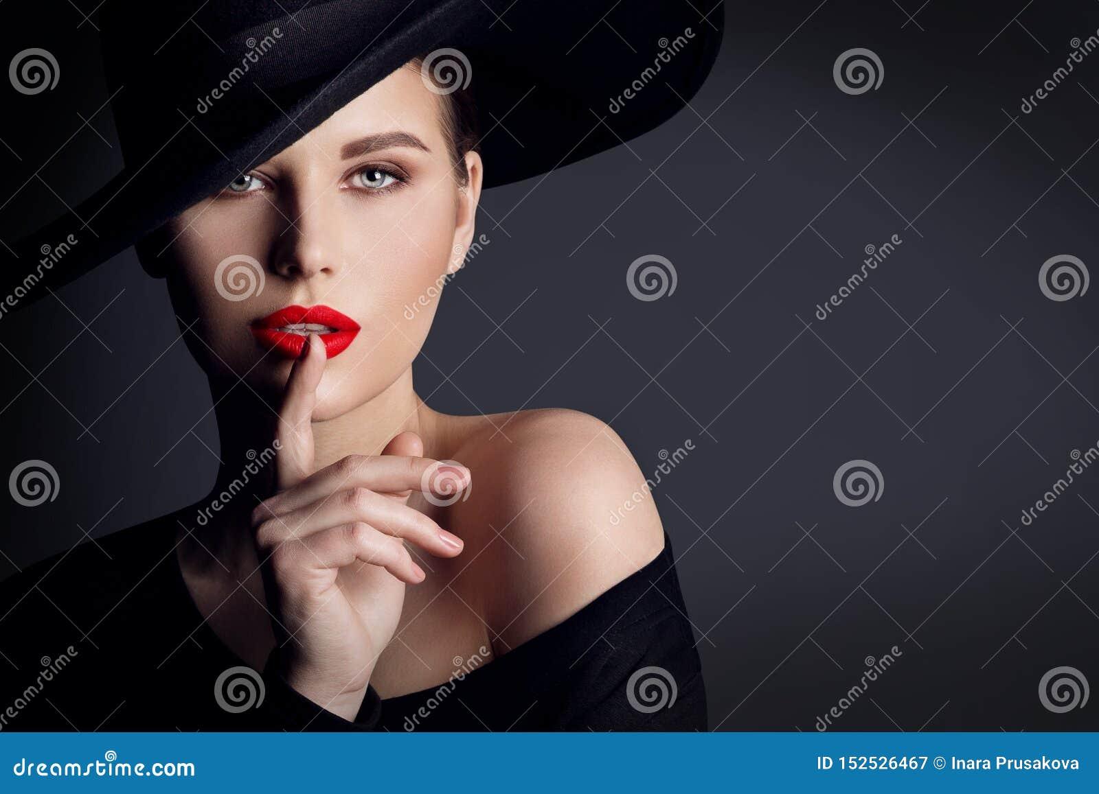 Μαύρο καπέλο γυναικών, κομψό πορτρέτο ομορφιάς μόδας πρότυπο, δάχτυλο στη χειλική σιωπηλή χειρονομία