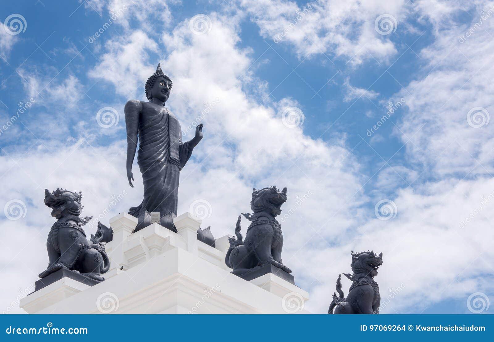 Μαύρο μεγάλο άγαλμα του Βούδα με άσπρους νεφελώδη και το μπλε ουρανό