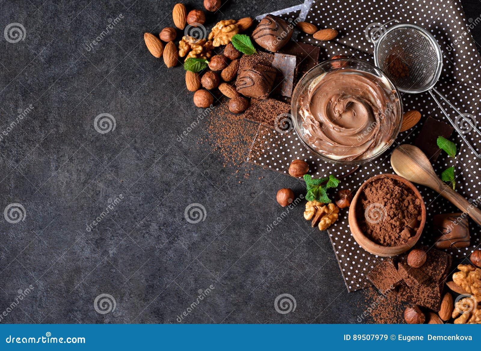 Μαύρο υπόβαθρο τροφίμων με το κακάο, τα καρύδια και τη σοκολάτα