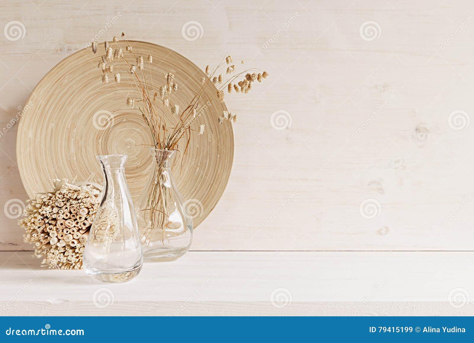 Μαλακό εγχώριο ντεκόρ του βάζου γυαλιού με spikelets και του ξύλινου πιάτου στο άσπρο ξύλινο υπόβαθρο
