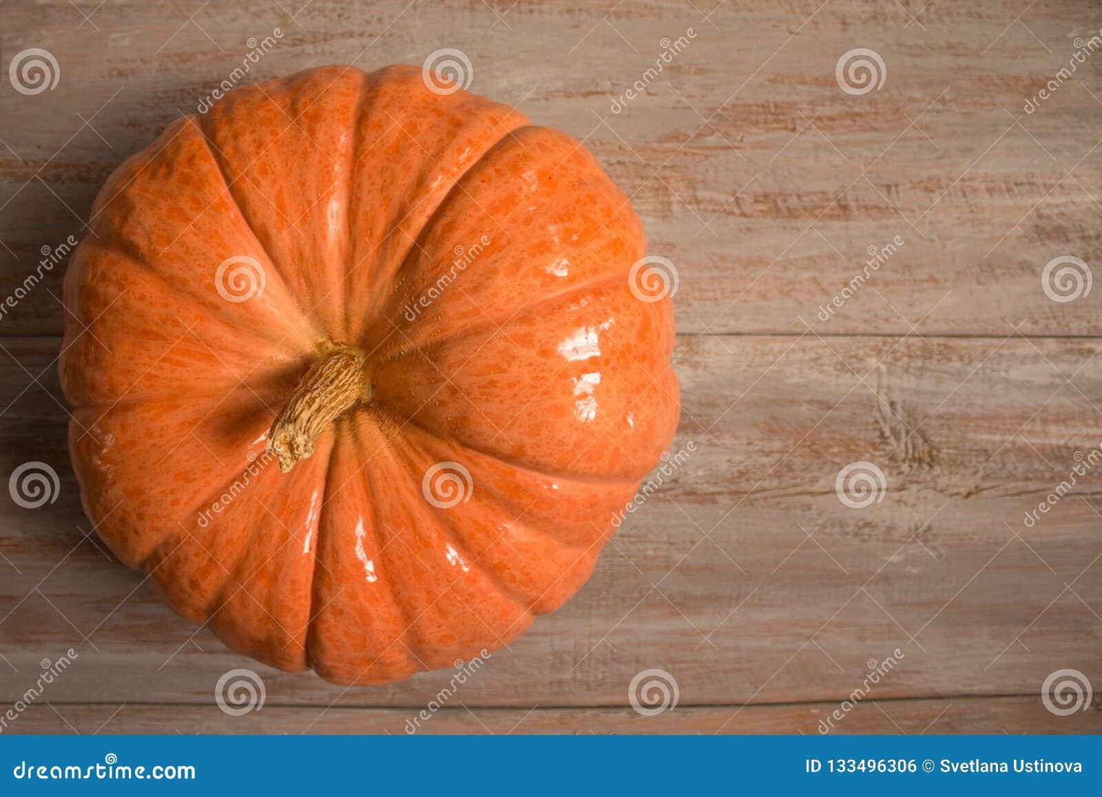 Μεγάλη πορτοκαλιά κολοκύθα στους ξύλινους πίνακες