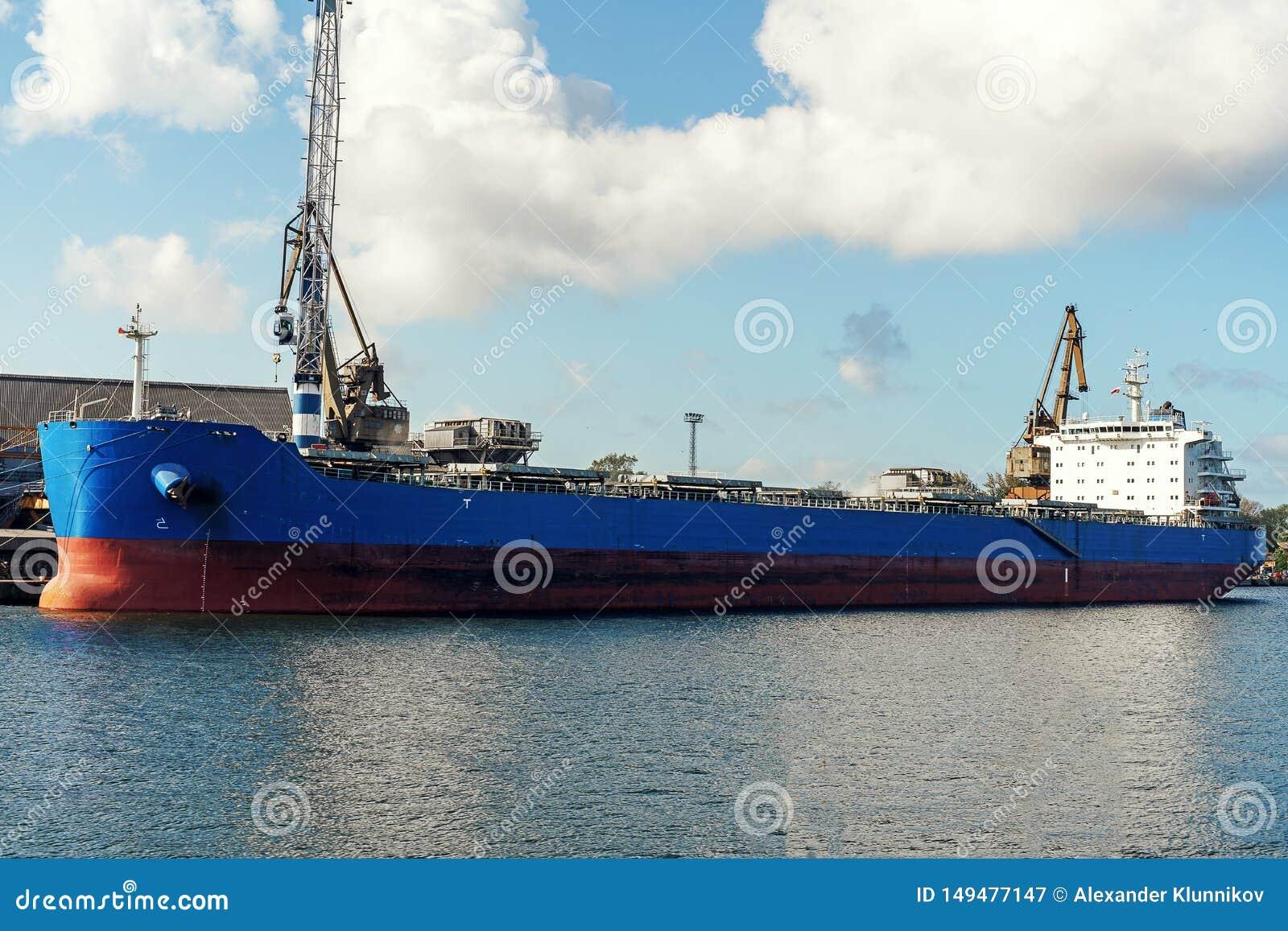 Μεγάλο μπλε φορτηγό πλοίο bulker που δένεται στο λιμένα φορτίου κατά τη διάρκεια της λειτουργίας φορτίου
