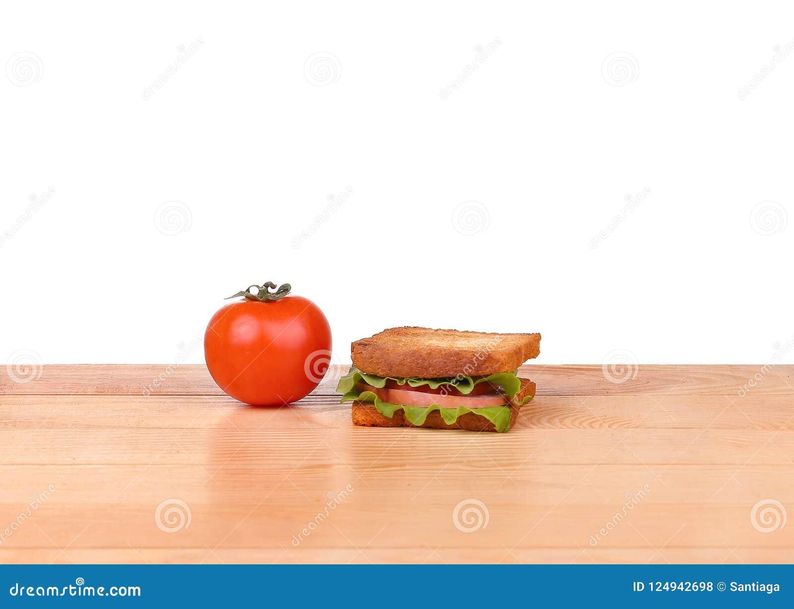 Μεγάλο σάντουιτς με τα φρέσκα λαχανικά στον ξύλινο πίνακα στο άσπρο υπόβαθρο