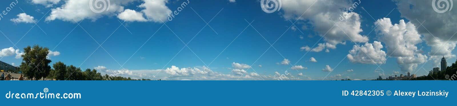 Μεγάλη άποψη πανοράματος του ουρανού με τα σύννεφα και τα δέντρα