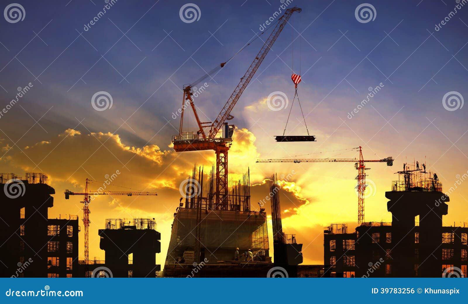 Μεγάλη οικοδόμηση γερανών και κτηρίου ενάντια στον όμορφο σκοτεινό ουρανό