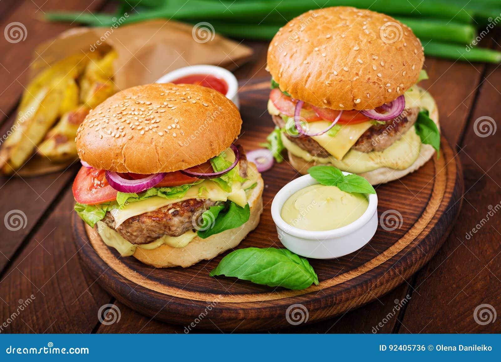 Μεγάλο σάντουιτς - χάμπουργκερ με juicy burger βόειου κρέατος, το τυρί, την ντομάτα, και το κόκκινο κρεμμύδι
