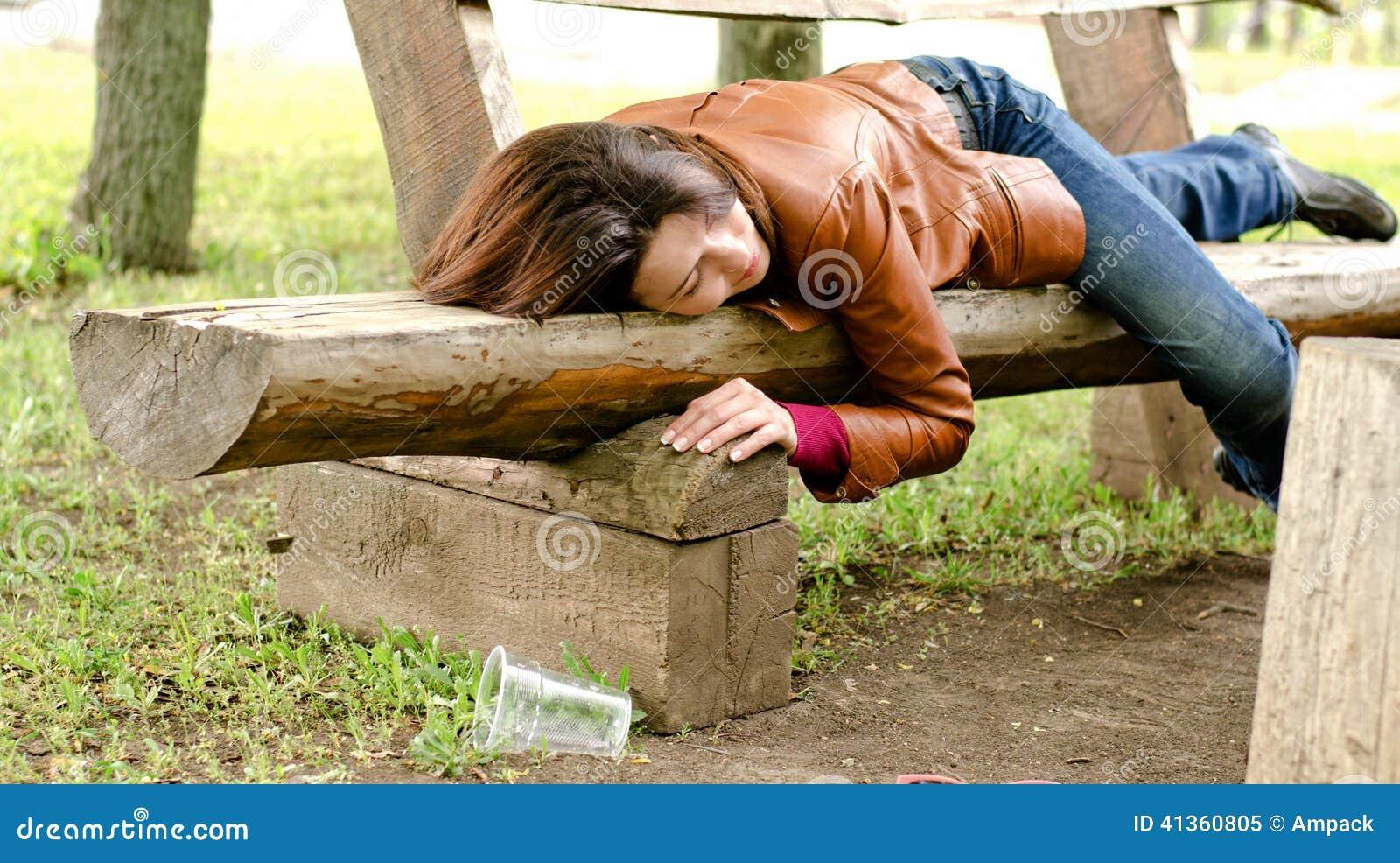 Μεθυσμένος ύπνος γυναικών αυτό μακριά σε έναν ξύλινο πάγκο