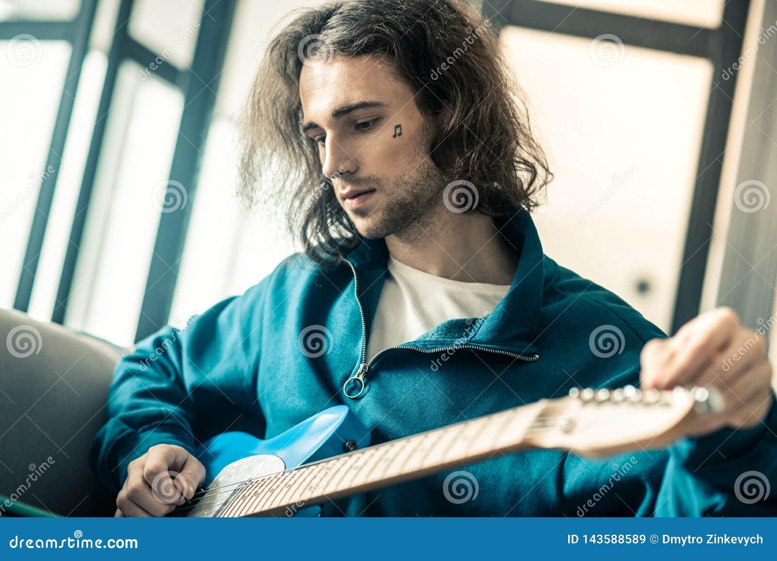 Μελαγχολικός μακρυμάλλης νέος μουσικός με τη μικρή δερματοστιξία που ελέγχει τις σειρές