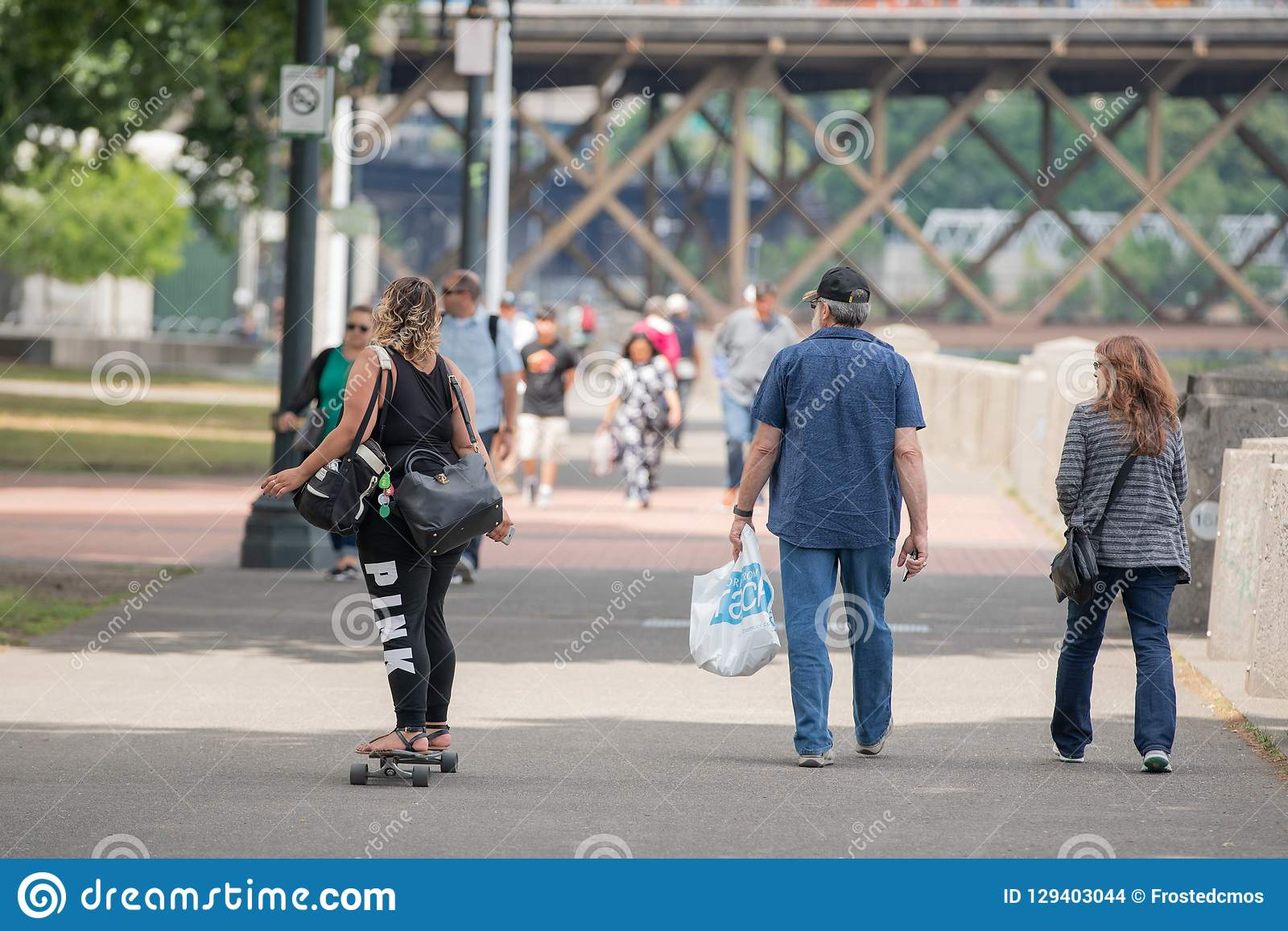 Μελαχροινή ξεφλουδισμένη γυναίκα με δύο τσάντες που οδηγούν skateboard