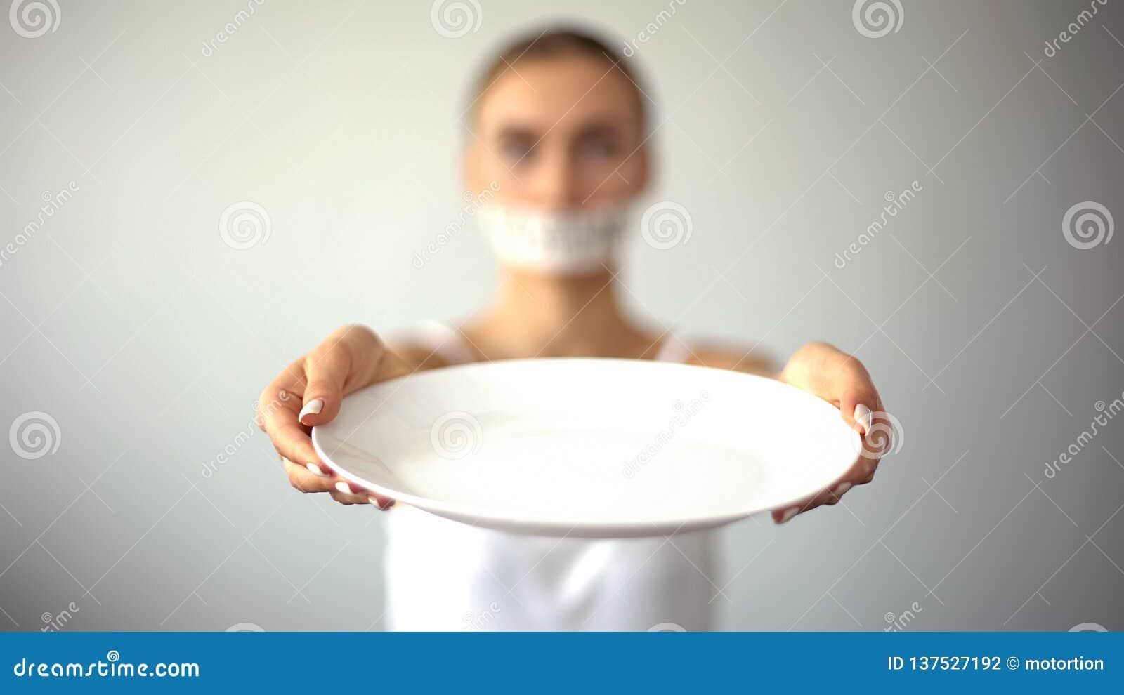 Μεμβρανοειδής γυναίκα με το δεμένο με ταινία στόμα που παρουσιάζει κενό πιάτο, έννοια της νηστείας, πείνα