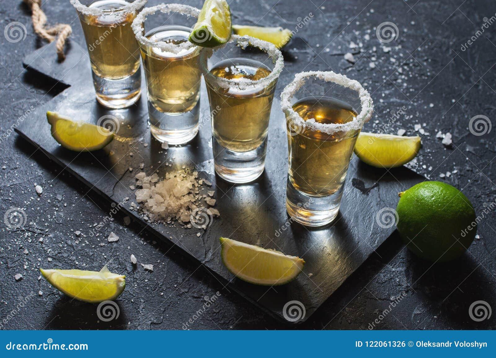 Μεξικάνικο χρυσό tequila με τον ασβέστη και άλας στο μαύρο υπόβαθρο πετρών