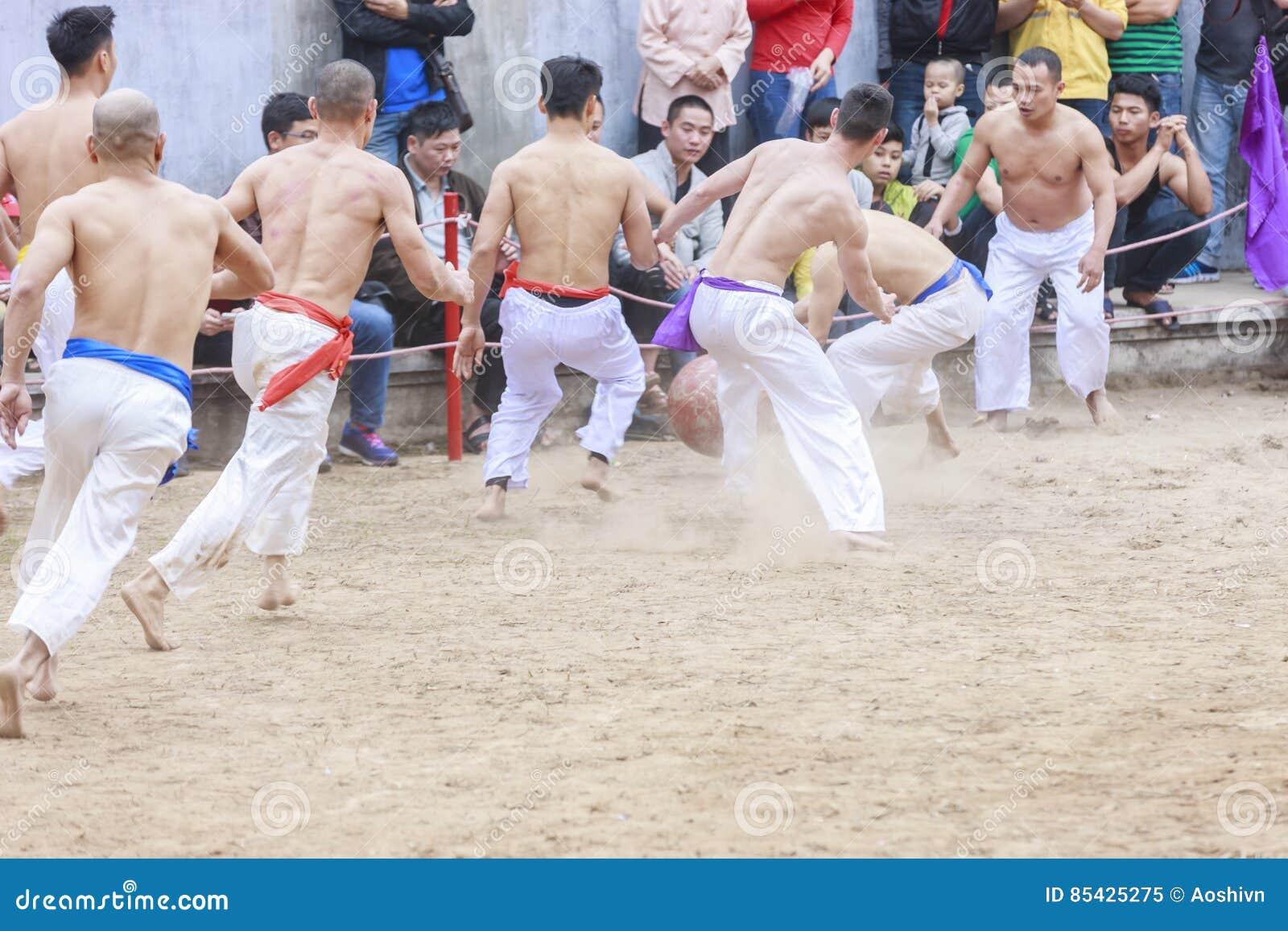 Μερικοί νεαροί άνδρες παίζουν με την ξύλινη σφαίρα στο σεληνιακό νέο έτος φεστιβάλ στο Ανόι, Βιετνάμ στις 27 Ιανουαρίου 2016