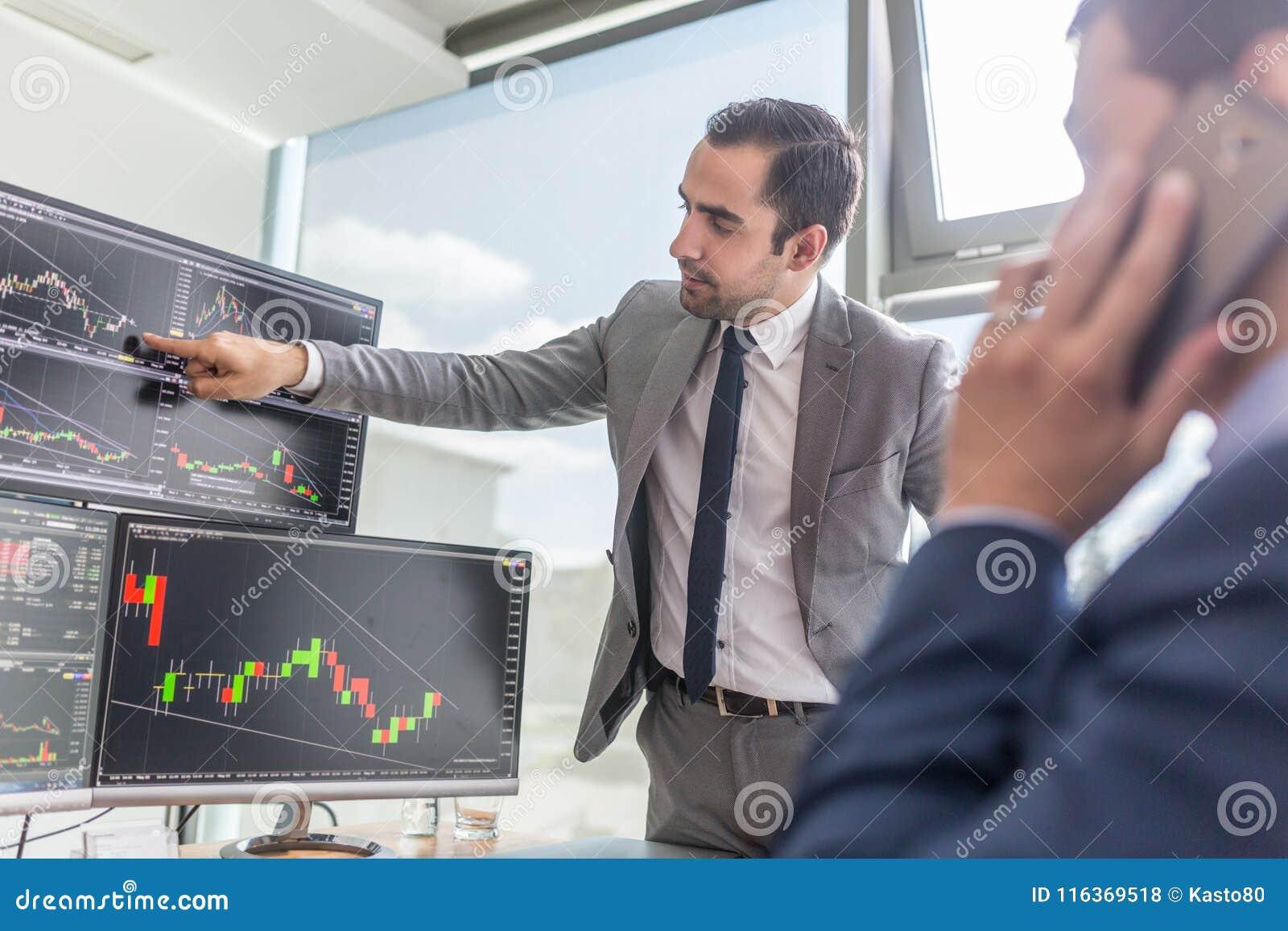 Μεσίτες αποθεμάτων που εξετάζουν τις οθόνες υπολογιστή, που κάνουν εμπόριο on-line