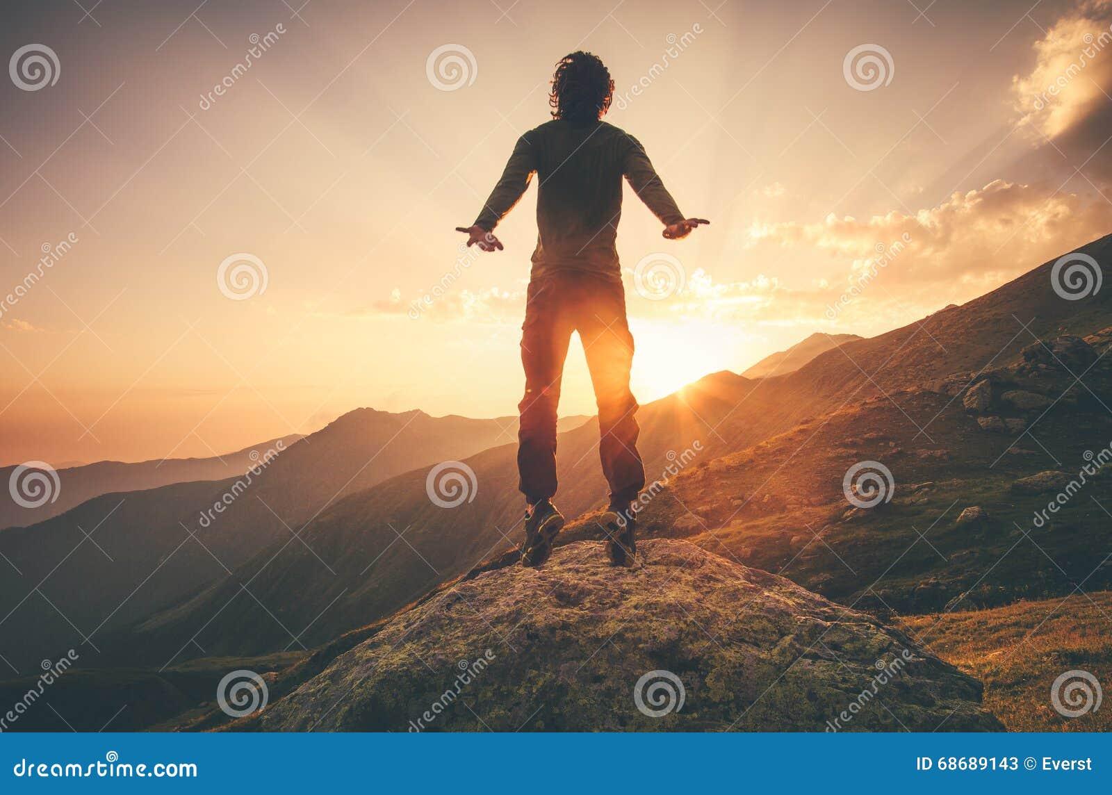 Μετεωρισμός πετάγματος νεαρών άνδρων που πηδά στα βουνά ηλιοβασιλέματος