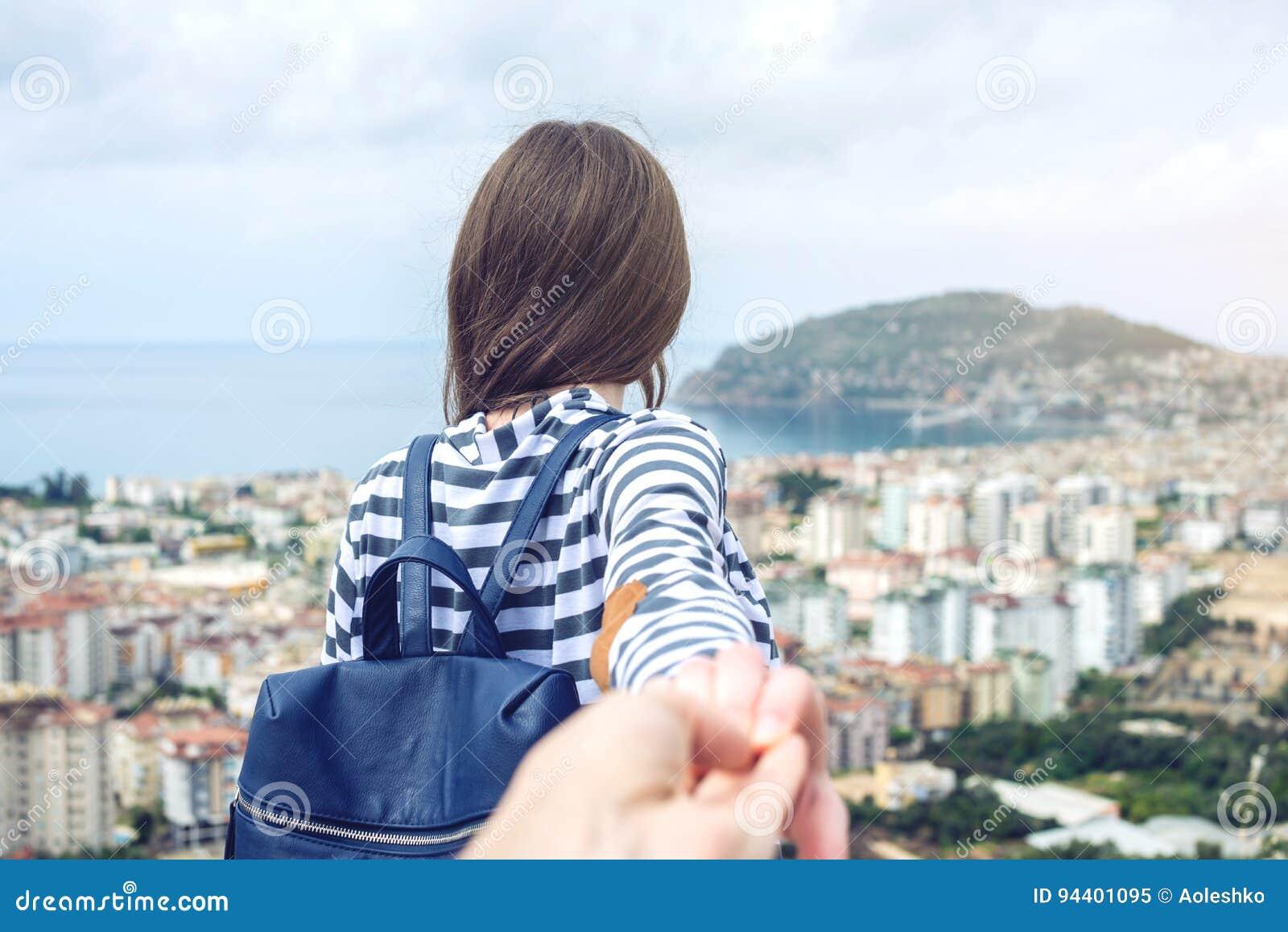 Με ακολουθήστε, ελκυστικό κορίτσι brunette που κρατά τους μολύβδους χεριών στην παράκτια πόλη από ένα ύψος