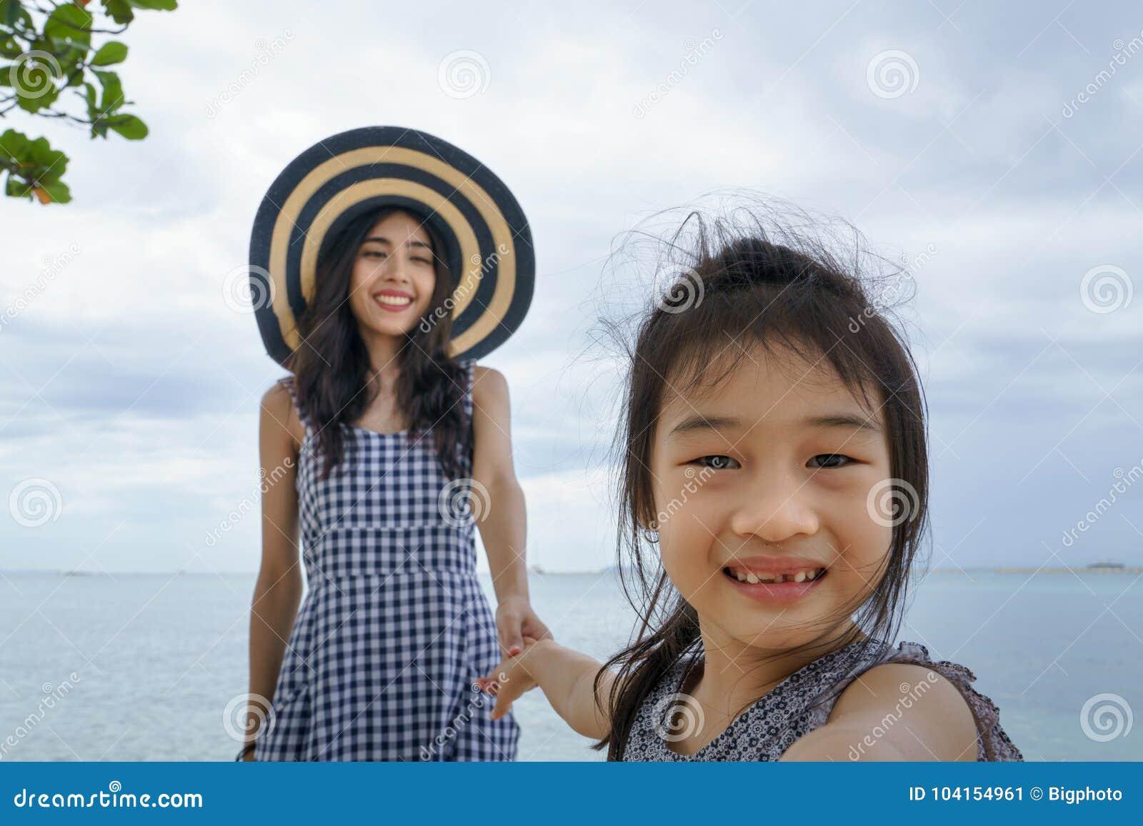 Μητέρα και η κόρη της που παίζουν στην παραλία
