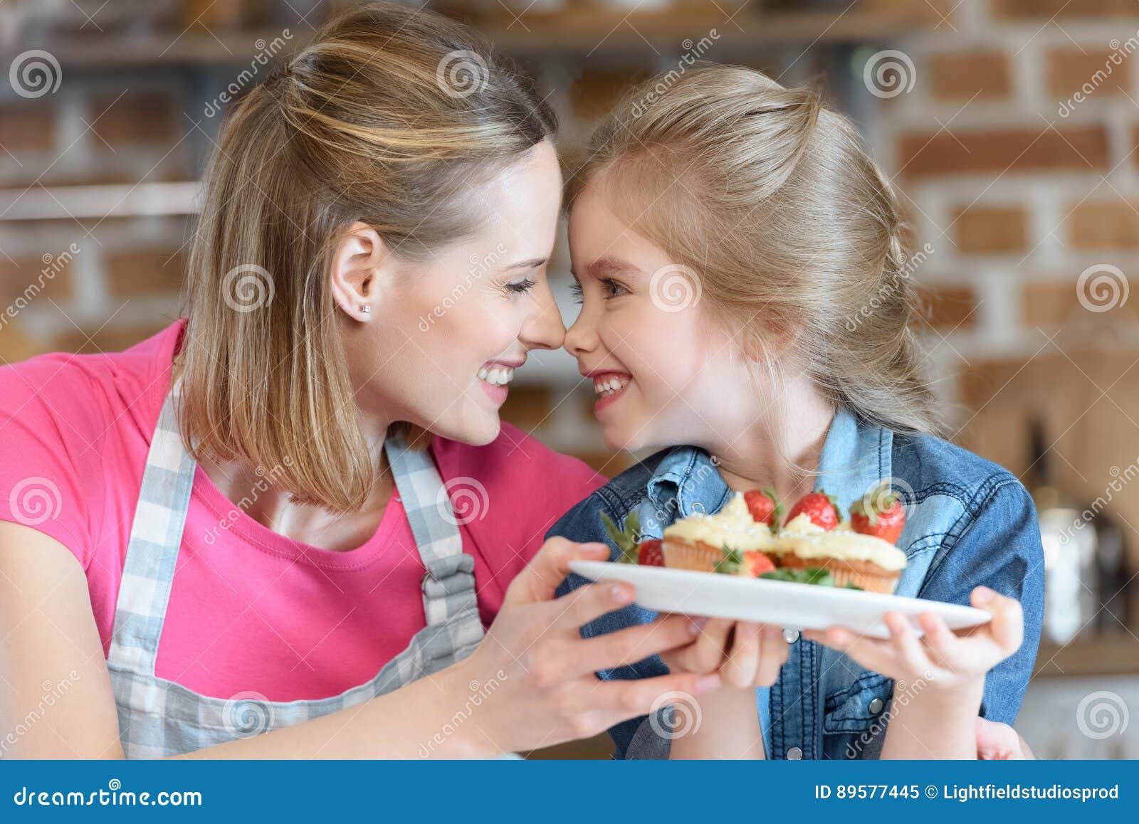 Μητέρα και κόρη που κρατούν τα σπιτικά cupcakes με τις φράουλες